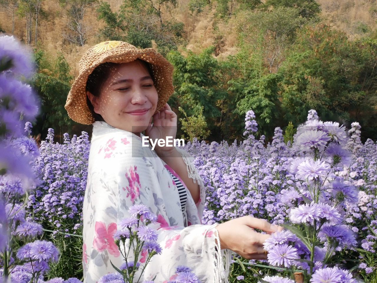 HAPPY WOMAN STANDING ON PURPLE FLOWERING PLANTS