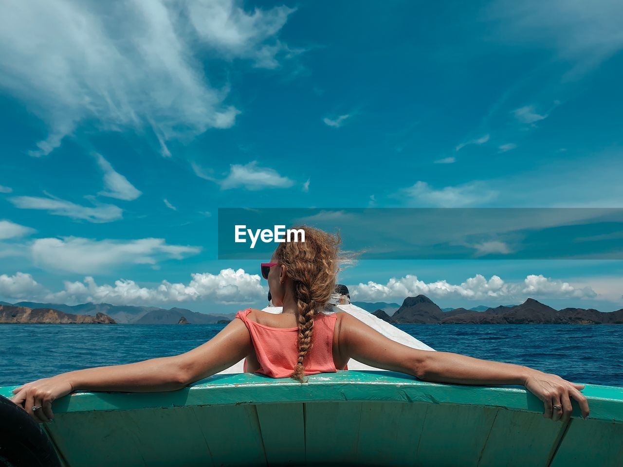Rear View Of Woman Sitting On Boat In Sea Against Blue Sky