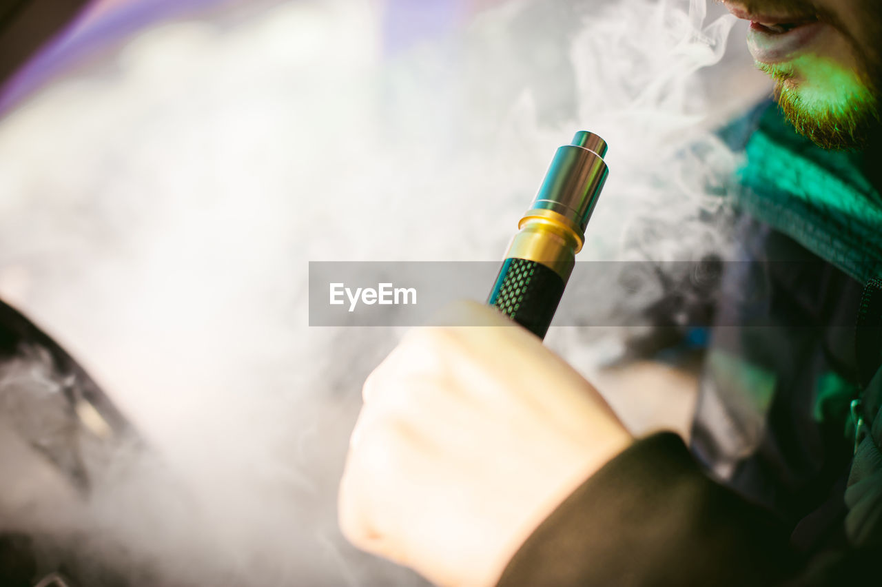 Midsection Of Man Smoking Electronic Cigarette