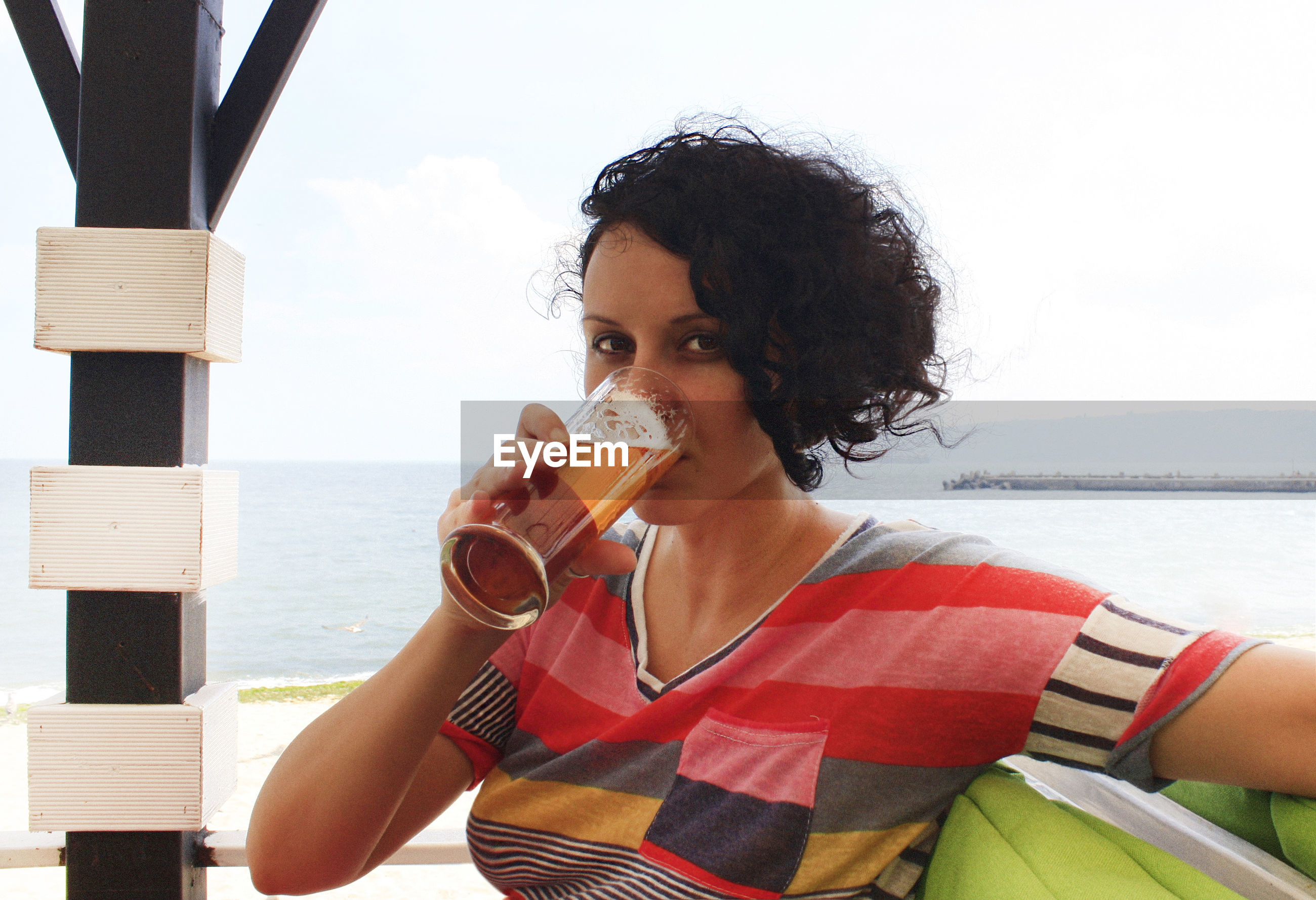 Portrait of woman drinking alcohol in glass against sea and sky