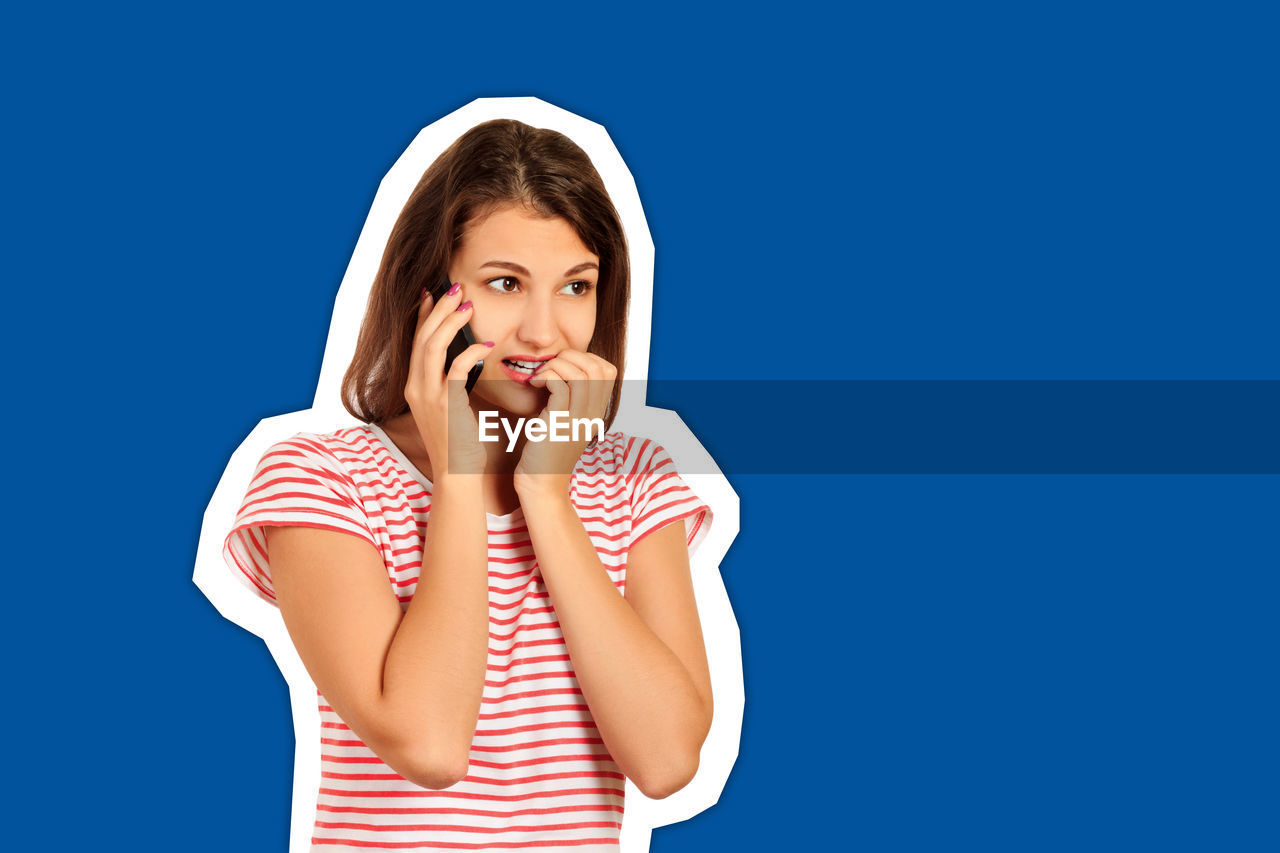 Shocked young woman talking over mobile phone cut out against blue background