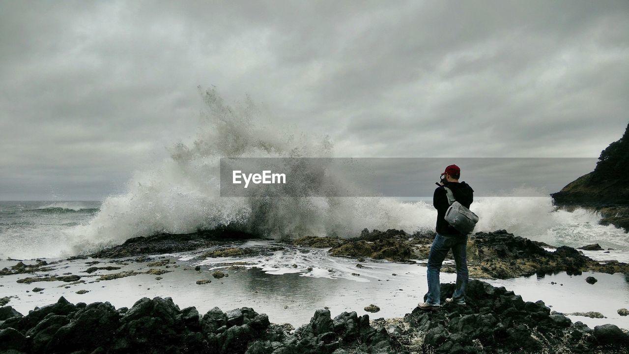 Person watching sea waves crashing on shore