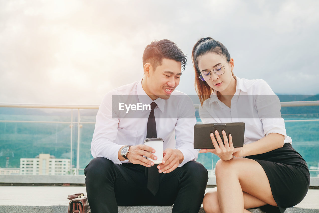 Businesswoman showing something on tablet to smiling colleague on balcony