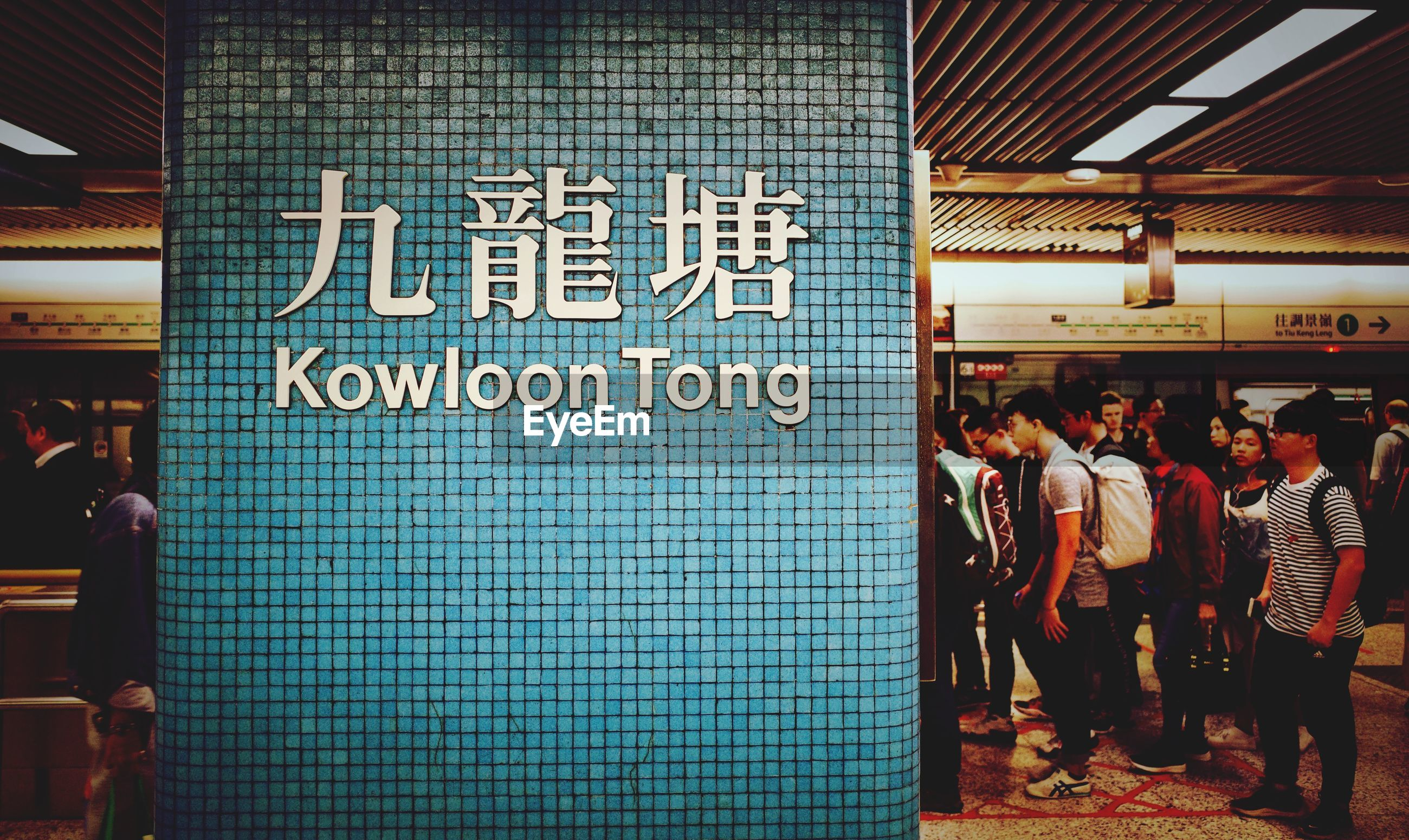 text, group of people, communication, western script, real people, subway station, sign, information, men, architecture, women, script, adult, non-western script, large group of people, information sign, built structure, public transportation, crowd, indoors, waiting