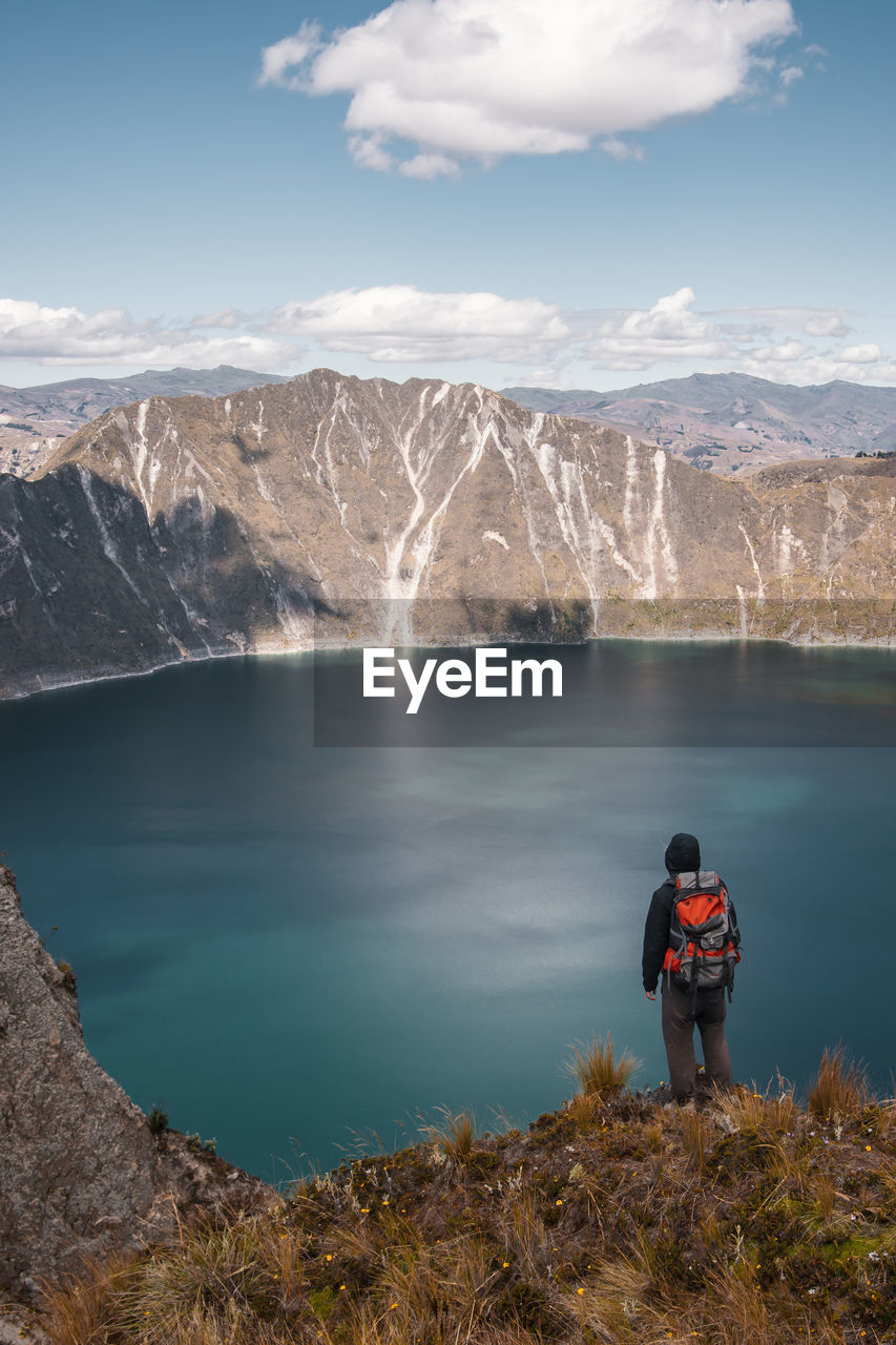 mountain, scenics - nature, beauty in nature, sky, leisure activity, real people, water, cloud - sky, nature, lifestyles, adventure, standing, hiking, rear view, holiday, day, tranquil scene, backpack, vacations, mountain range, looking at view, outdoors