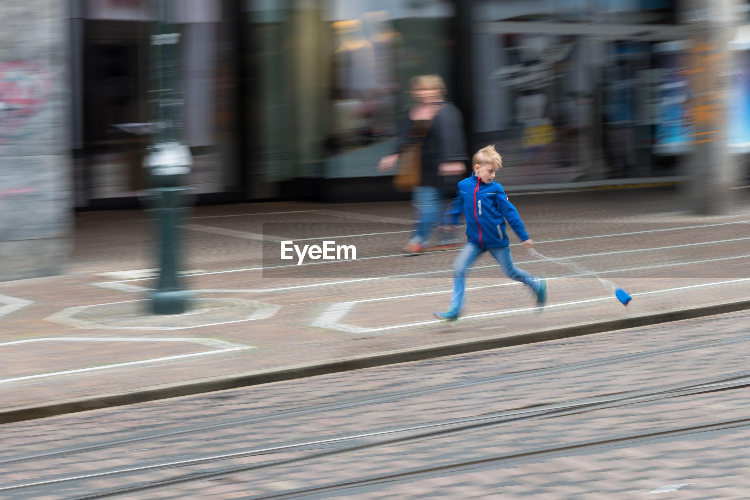 Boy running with yo-yo on footpath