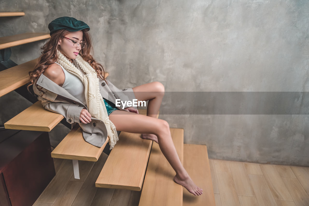 Full length of young woman sitting on steps at home
