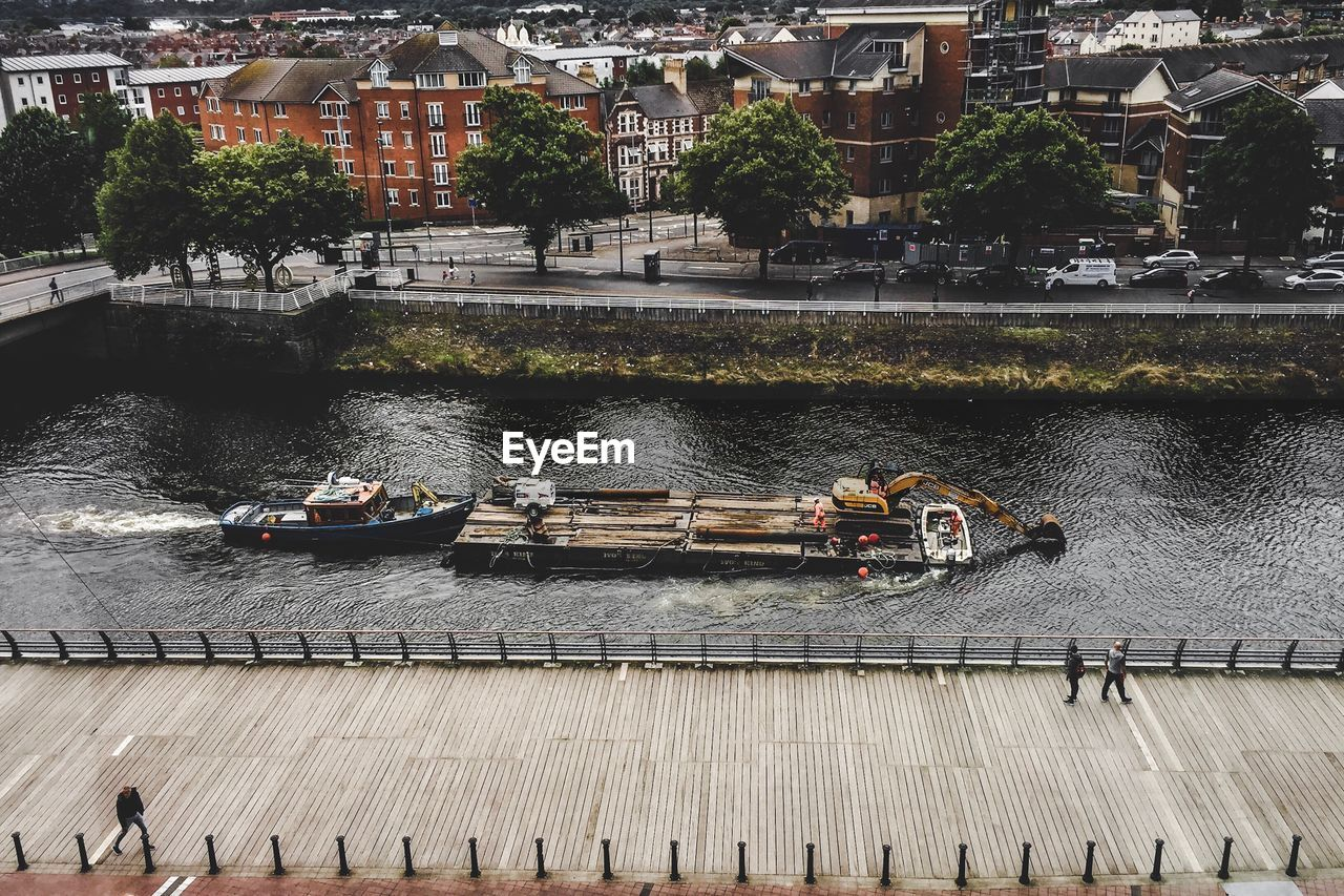 nautical vessel, transportation, water, mode of transportation, architecture, built structure, river, day, real people, group of people, nature, crowd, building exterior, high angle view, plant, tree, large group of people, outdoors