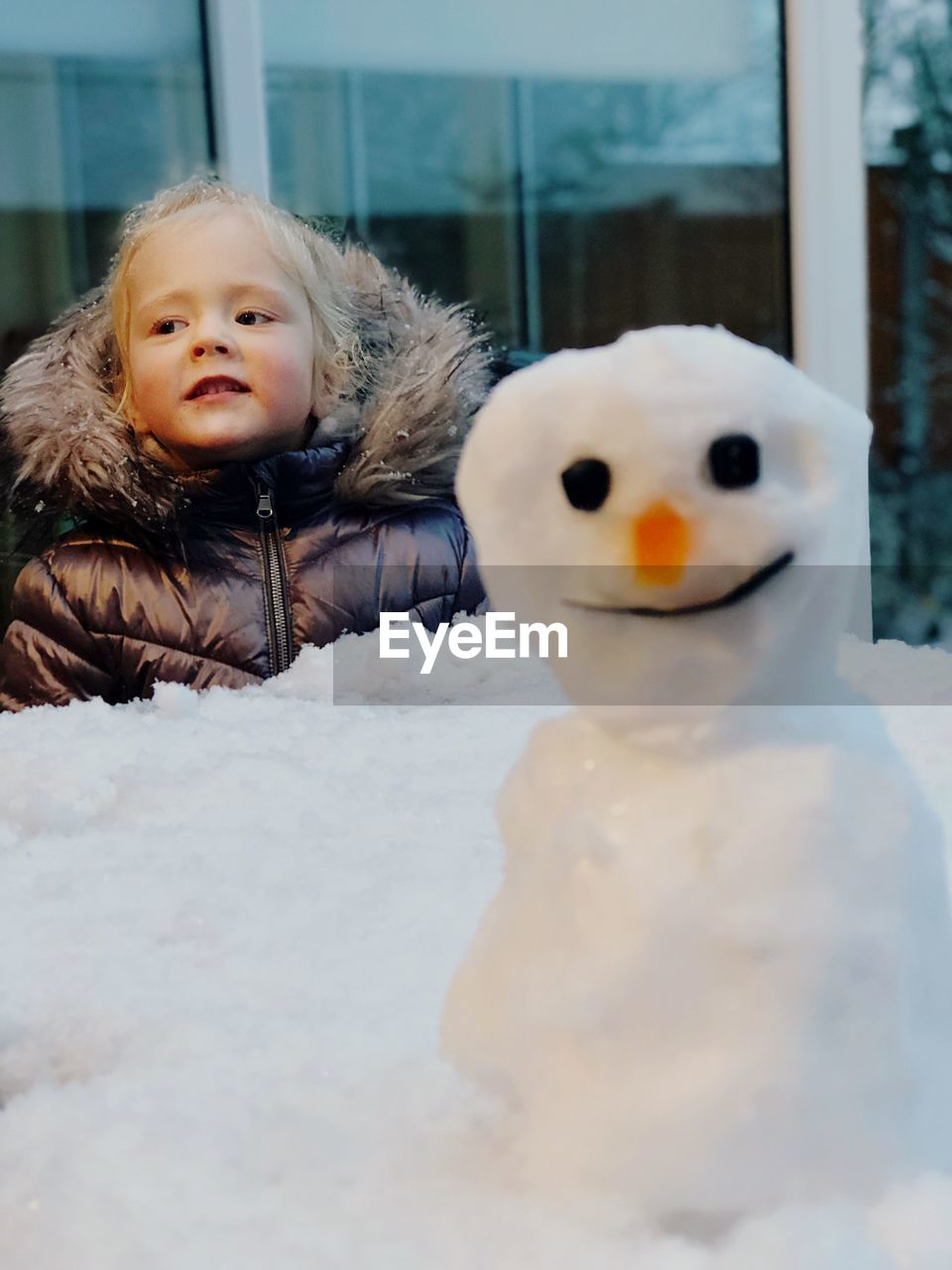 Close-Up Of Snowman With Girl In Background