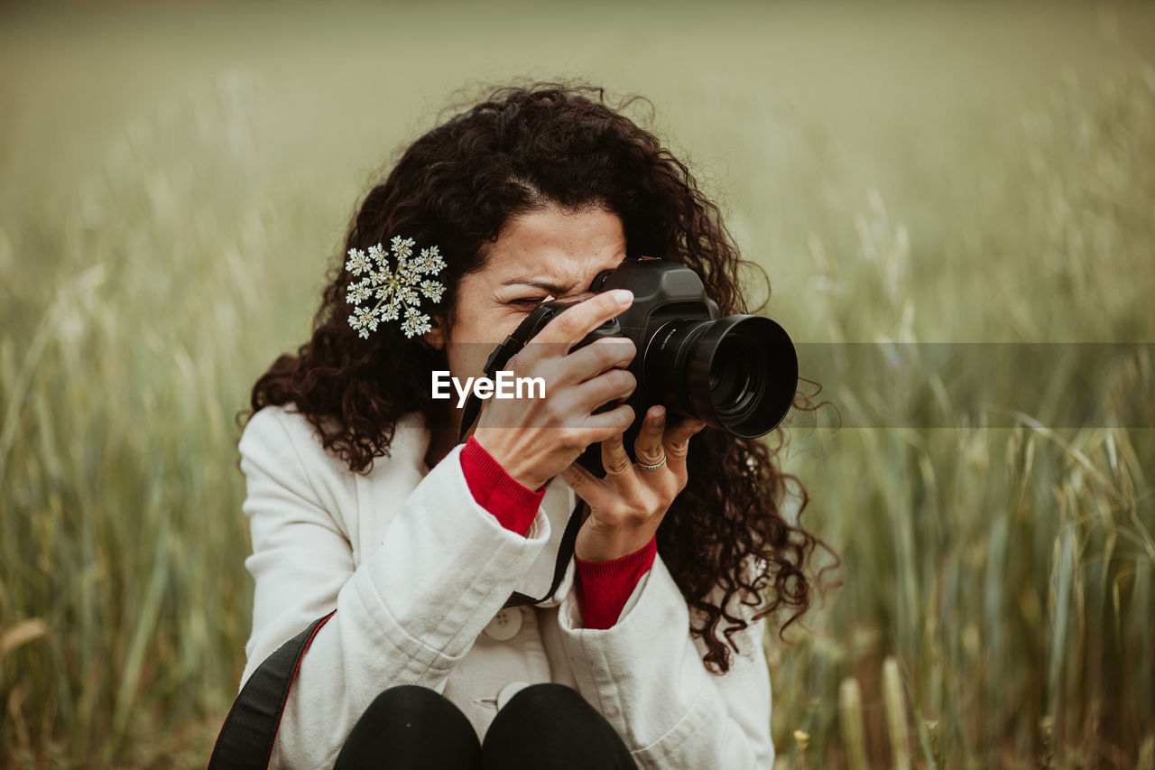 camera - photographic equipment, photography themes, real people, one person, photographic equipment, leisure activity, photographing, holding, activity, technology, plant, camera, field, lifestyles, occupation, digital camera, photographer, land, young adult, hairstyle, digital single-lens reflex camera, outdoors, slr camera