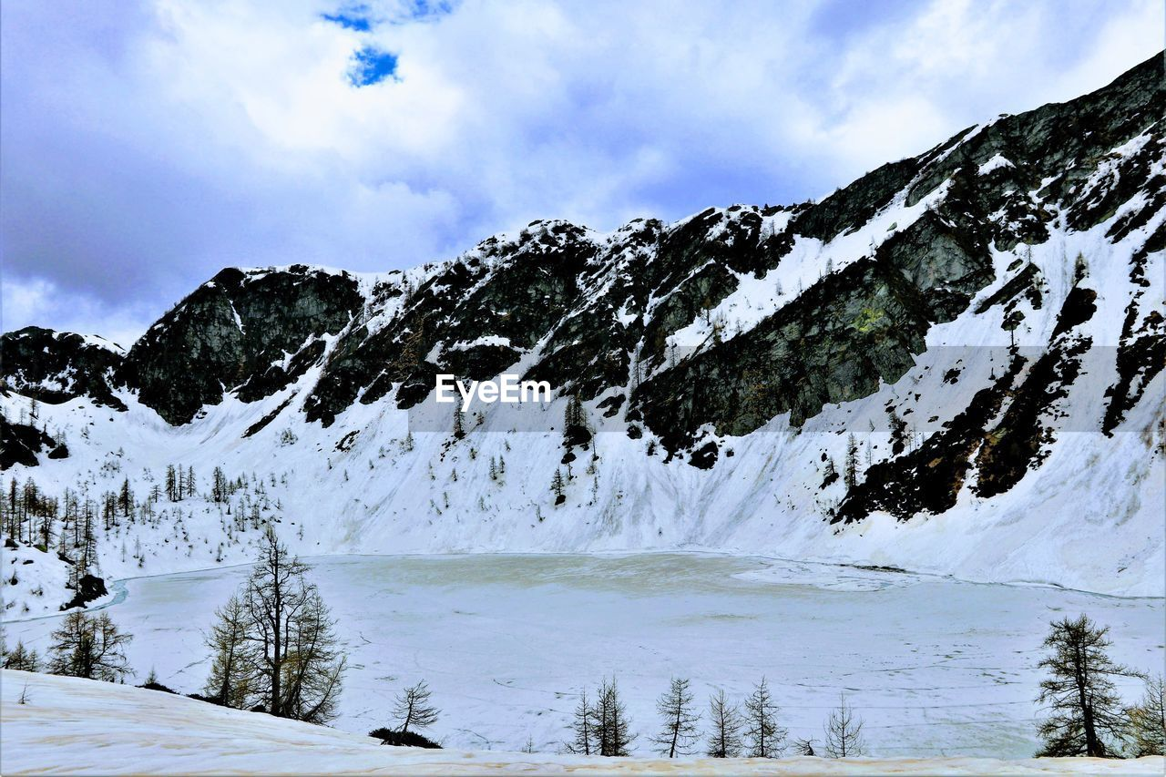 winter, cold temperature, snow, sky, beauty in nature, cloud - sky, scenics - nature, tranquil scene, tree, tranquility, mountain, plant, white color, non-urban scene, nature, no people, snowcapped mountain, day, environment, mountain range