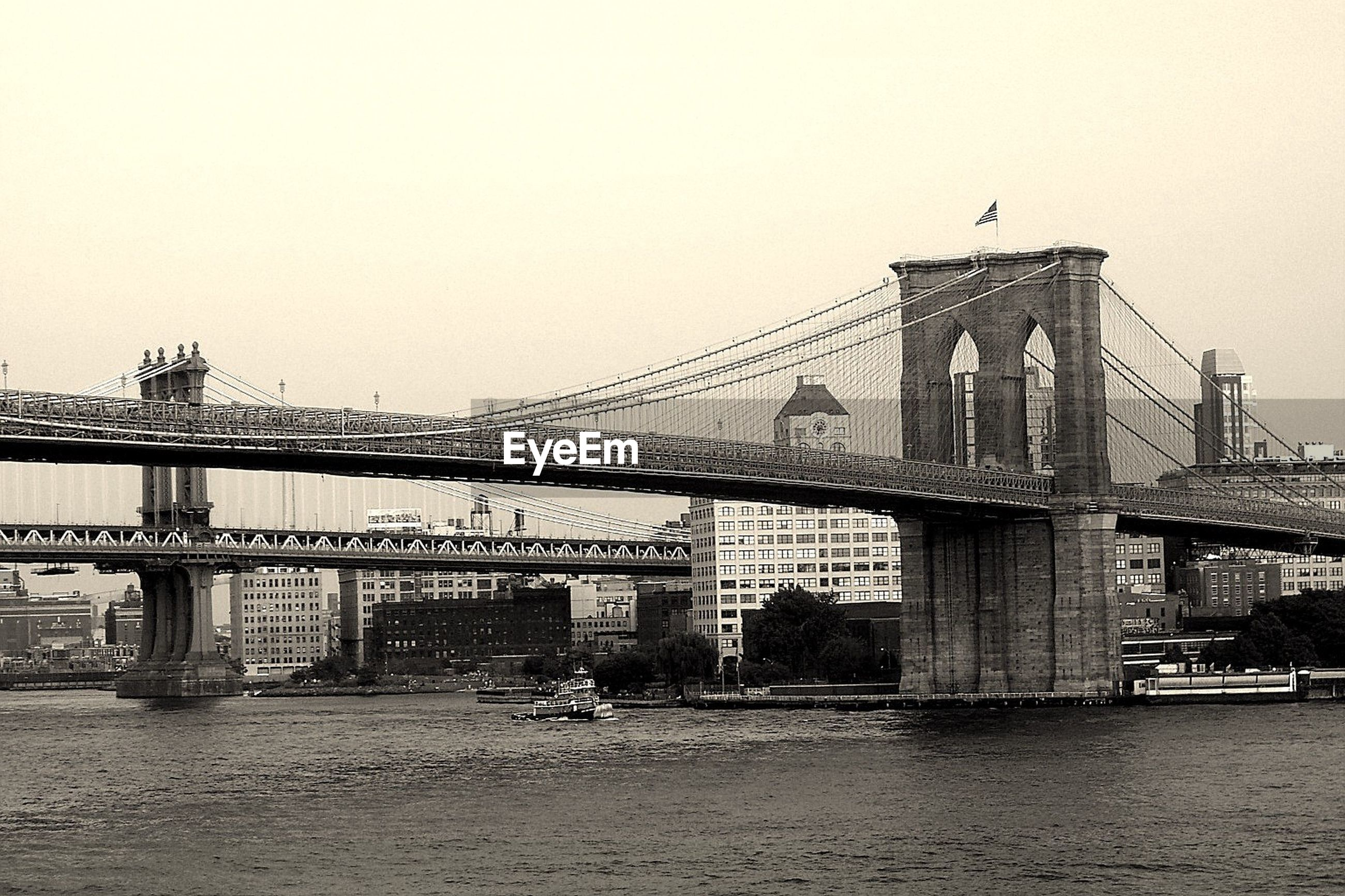 Low angle view of brooklyn bridge over river against clear sky in city