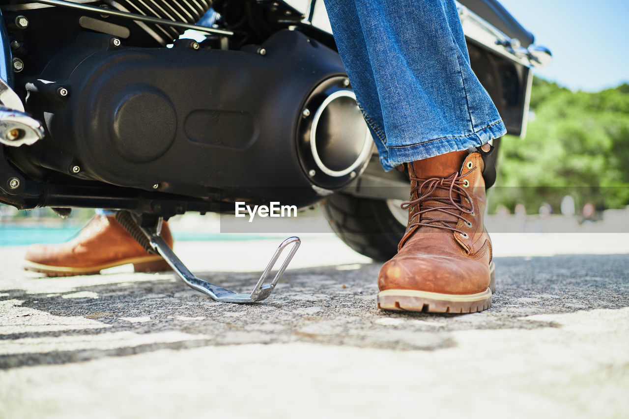 LOW SECTION OF WOMAN WEARING CANVAS SHOES ON MOTORCYCLE