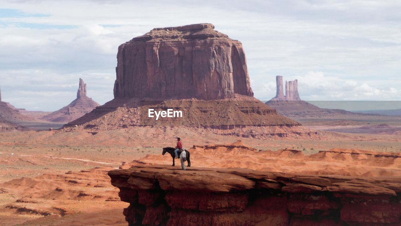 People With Horse On Cliff At Monument Valley Against Sky