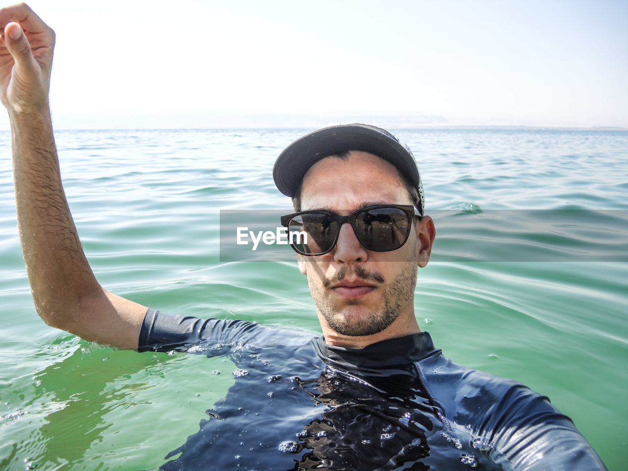 Portrait Of Young Man Wearing Sunglasses Swimming In Sea Against Sky