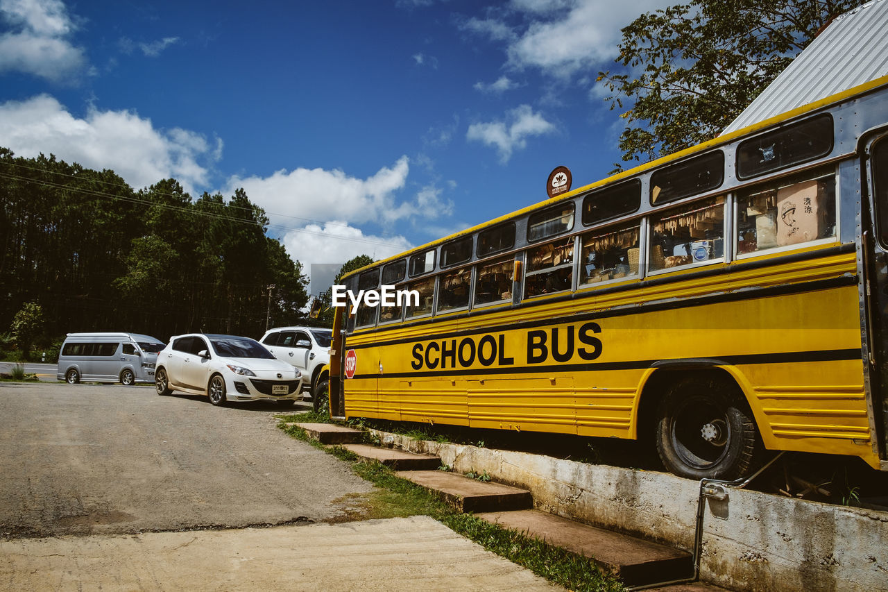 transportation, mode of transport, land vehicle, sky, school bus, text, yellow, cloud - sky, bus, day, outdoors, communication, tree, road, no people