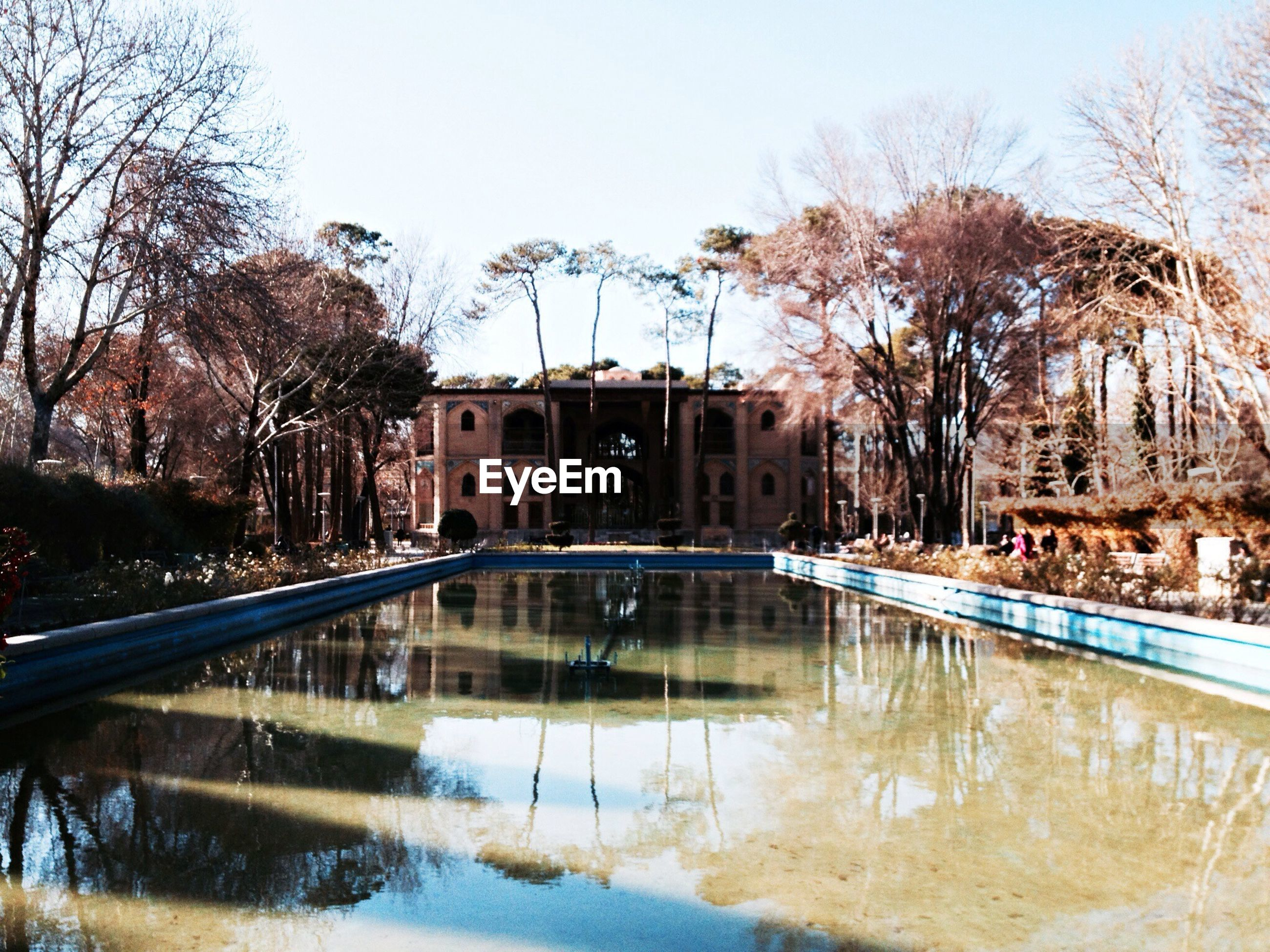 architecture, building exterior, water, built structure, reflection, tree, waterfront, bare tree, river, canal, city, clear sky, building, lake, sky, residential building, standing water, pond, day, residential structure