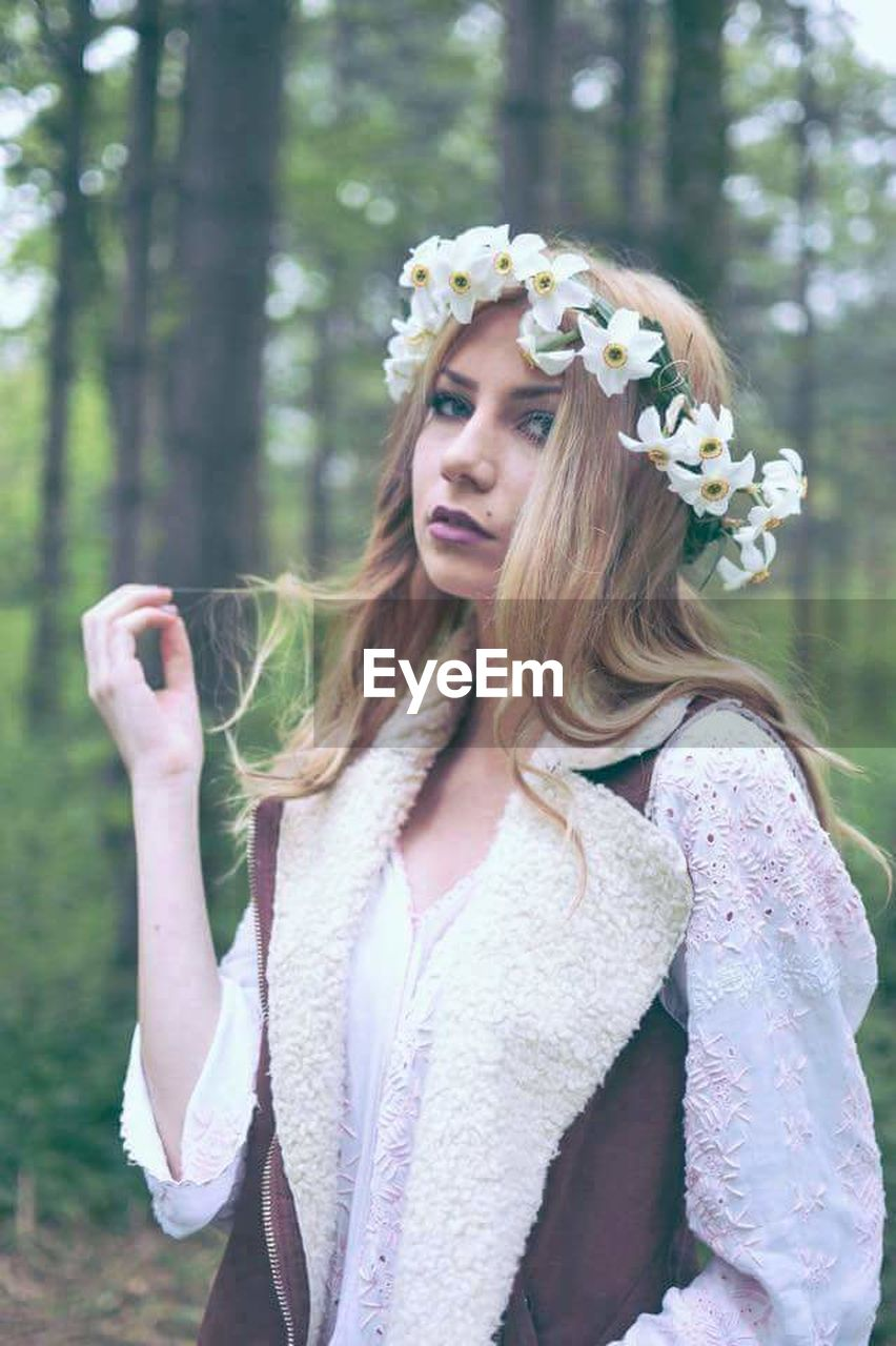 young adult, one person, flower, long hair, day, forest, one young woman only, wearing flowers, outdoors, focus on foreground, blond hair, beautiful woman, one woman only, only women, nature, young women, tree, adults only, adult, people, close-up