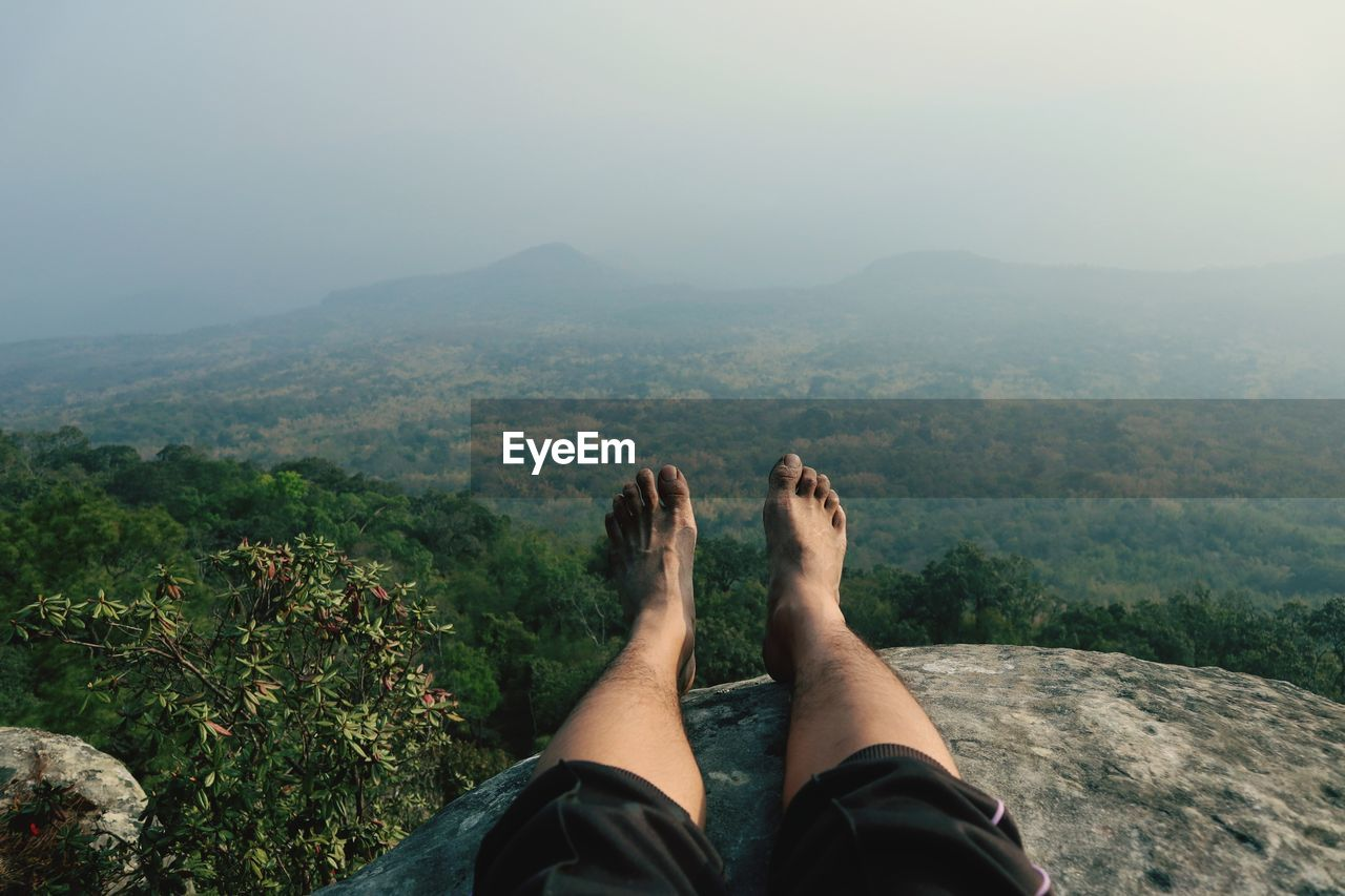 low section, human leg, personal perspective, real people, mountain, human body part, one person, body part, beauty in nature, nature, leisure activity, scenics - nature, lifestyles, plant, sky, day, relaxation, environment, barefoot, human foot, outdoors