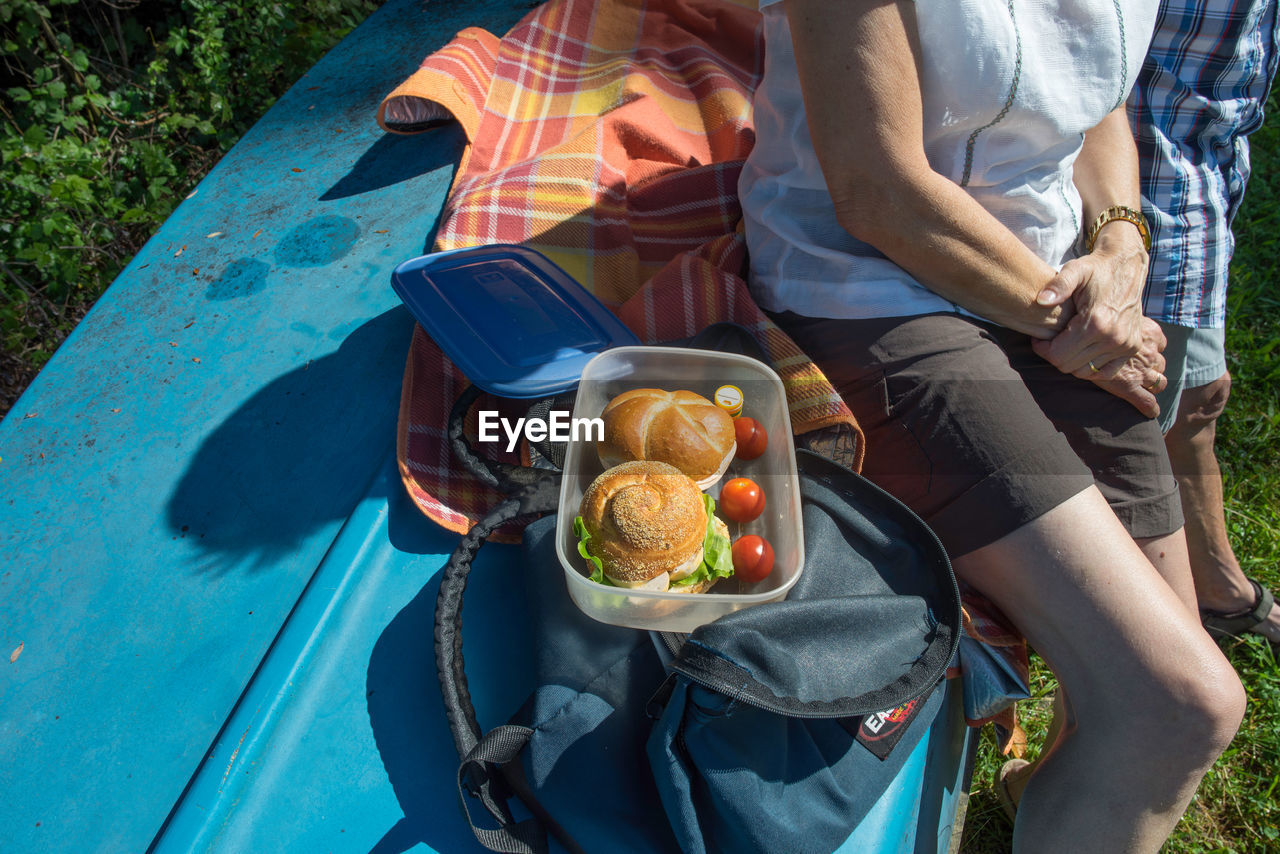 High Angle View Of Senior Couple With Burgers In Container Sitting On Upside Down Boat