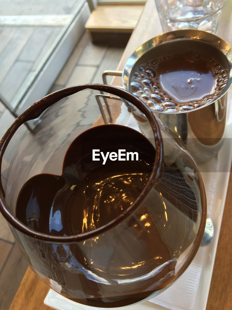 High angle view of hot chocolate in wineglass and drinking glass