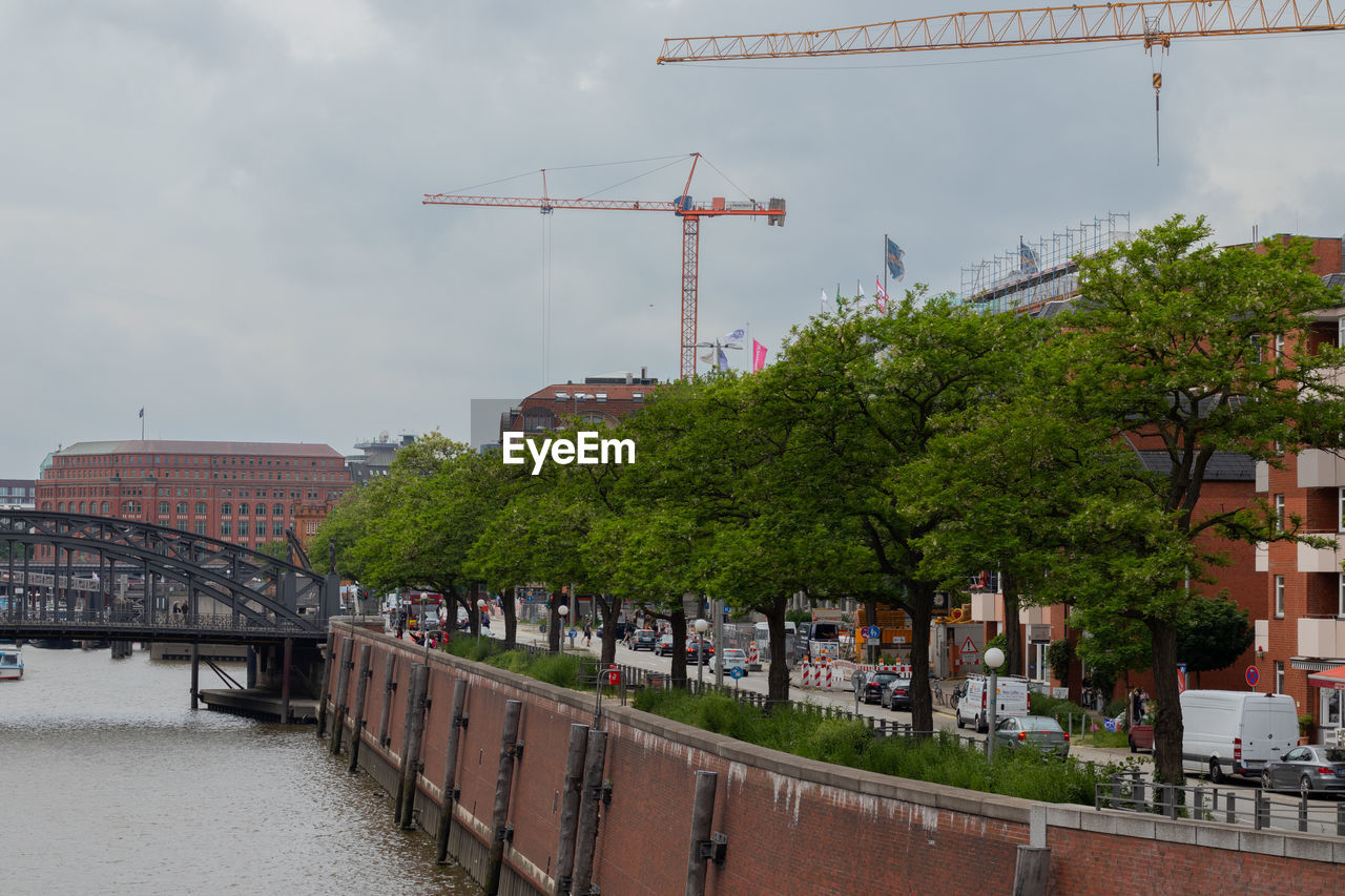 architecture, built structure, building exterior, sky, bridge, tree, city, plant, transportation, nature, water, connection, bridge - man made structure, day, machinery, river, construction industry, cloud - sky, development, outdoors, no people, construction equipment