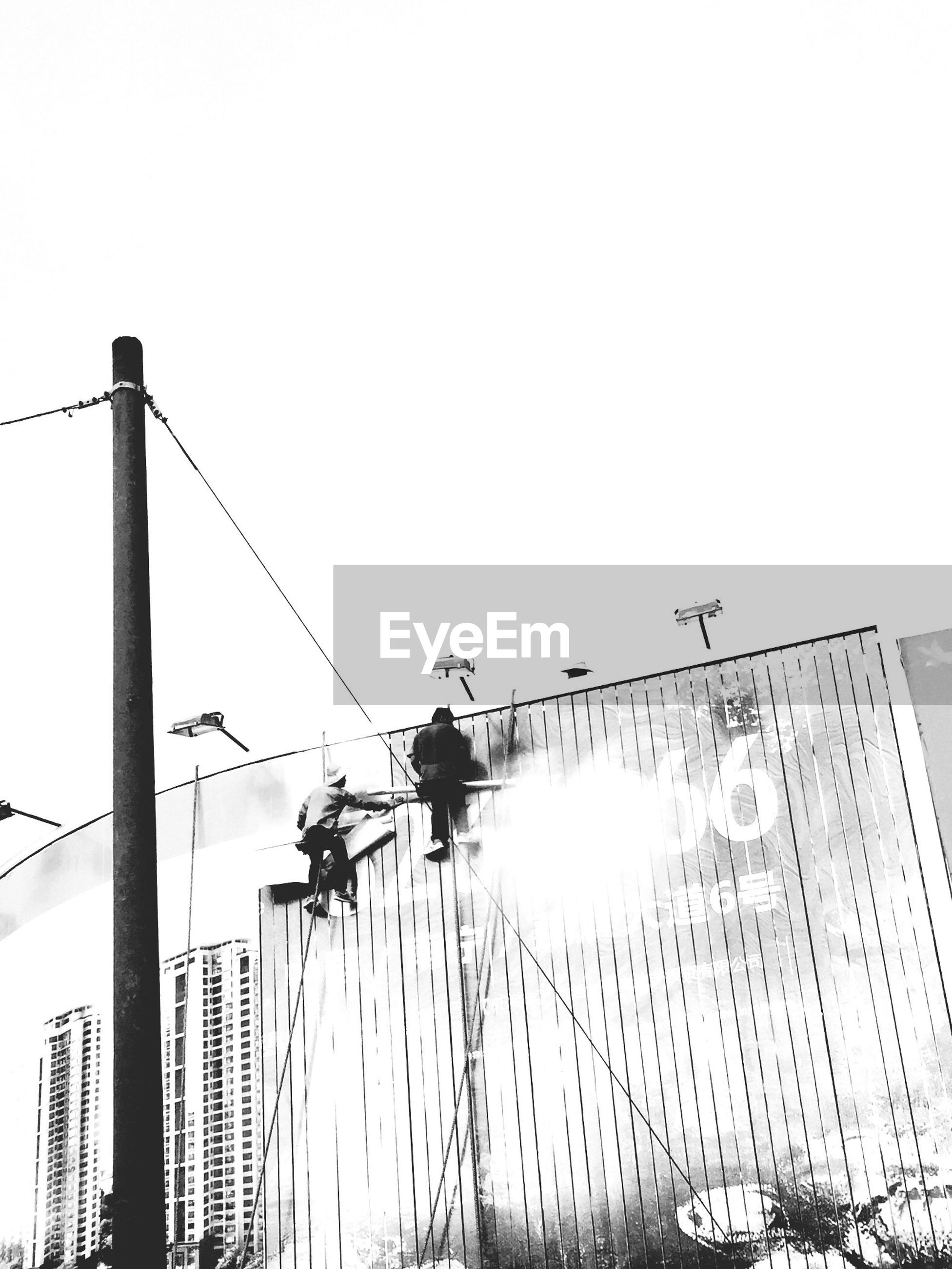 low angle view, building exterior, clear sky, built structure, architecture, street light, silhouette, copy space, building, sky, city, power line, crane - construction machinery, construction site, outdoors, lighting equipment, cable, development, no people, electricity