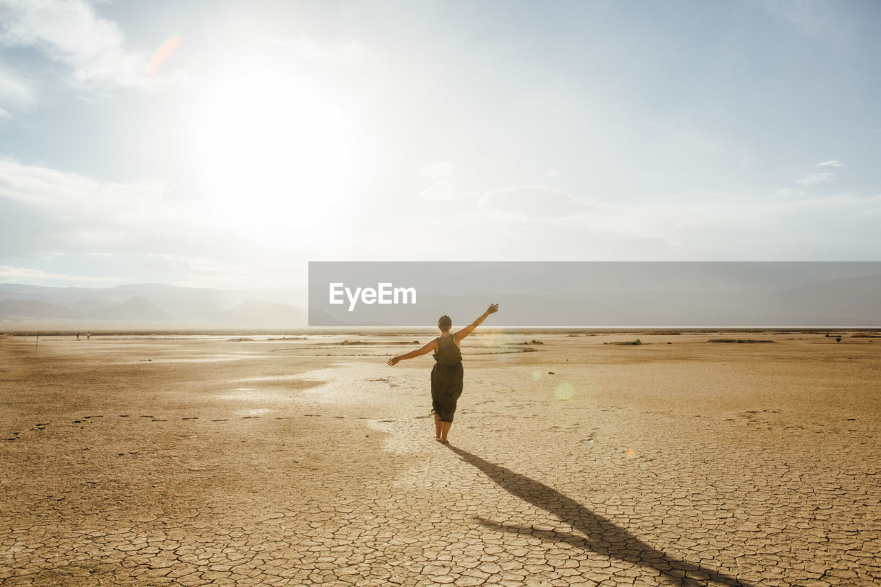 Woman With Arms Outstretched In Desert Against Sky