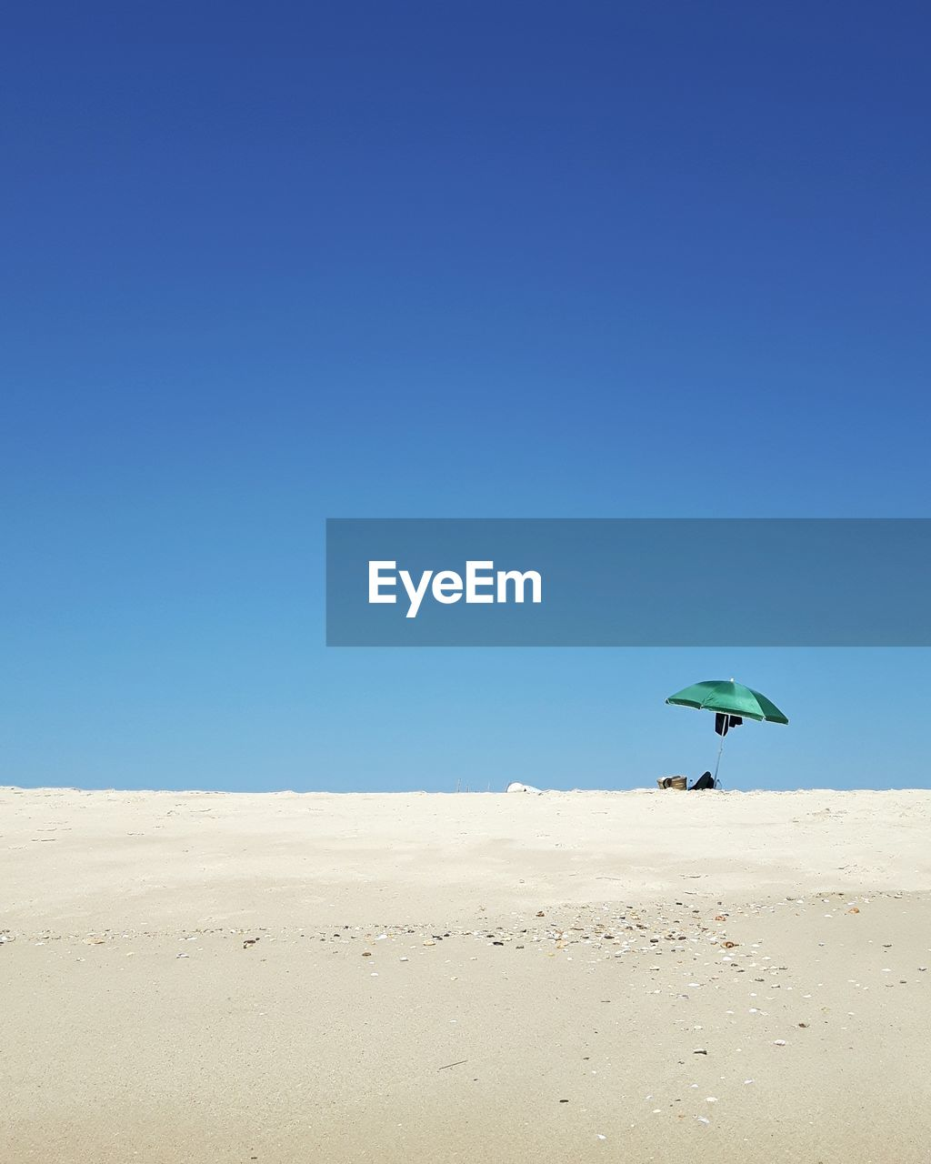 SCENIC VIEW OF SAND DUNE AGAINST CLEAR BLUE SKY