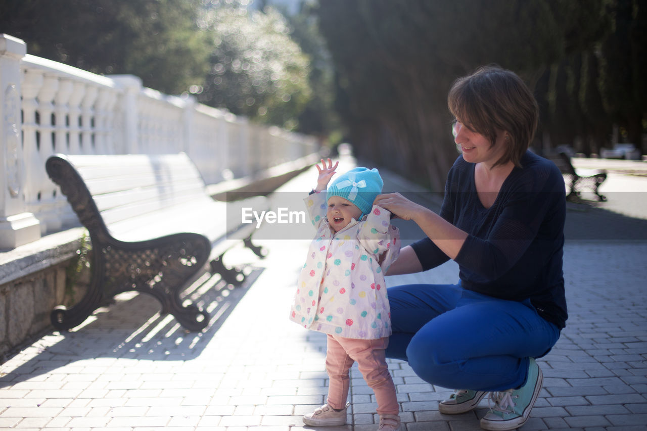 MOTHER AND DAUGHTER WITH ARMS OUTSTRETCHED ON FLOOR