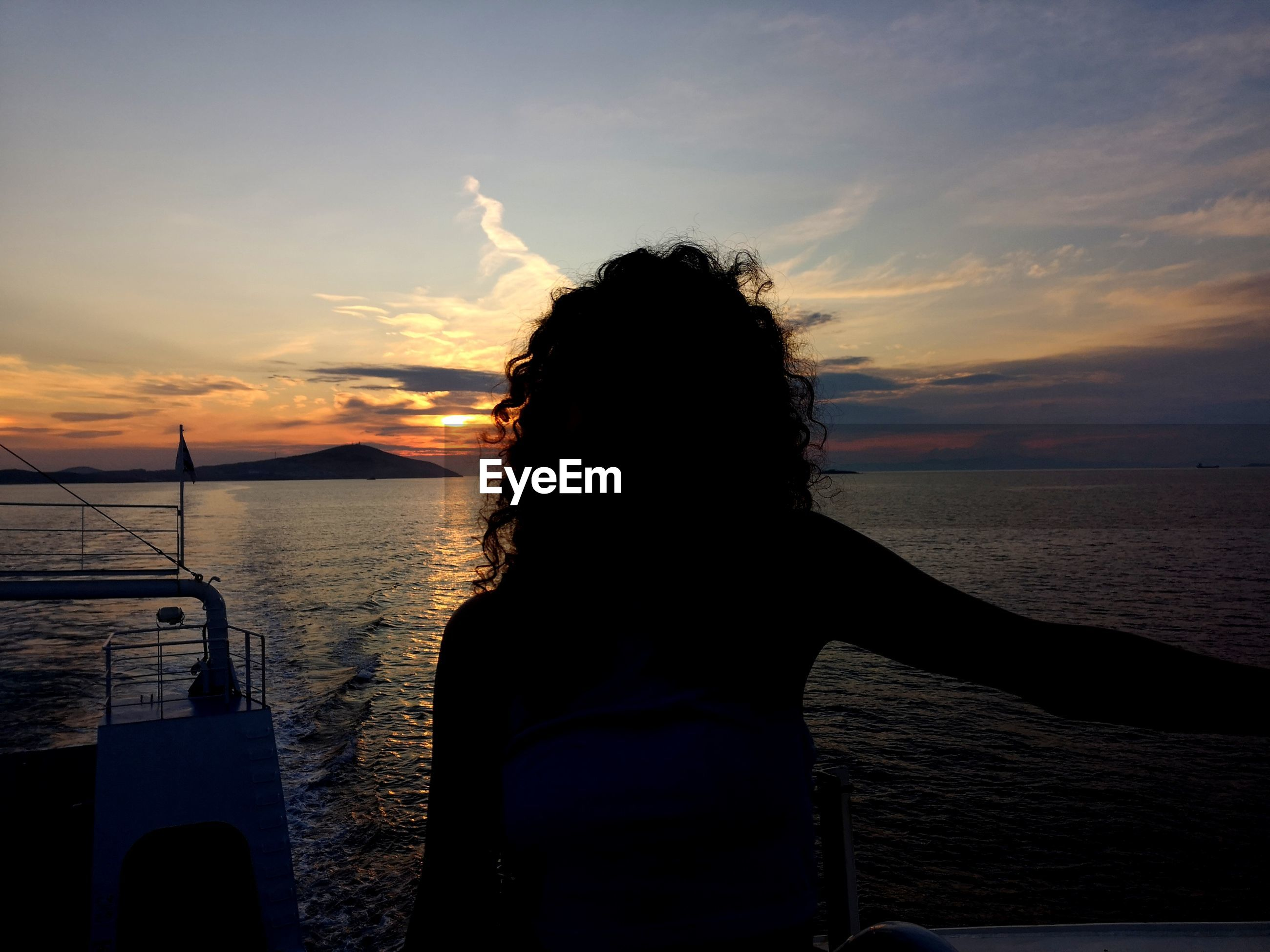 Rear view of woman at beach against sky during sunset