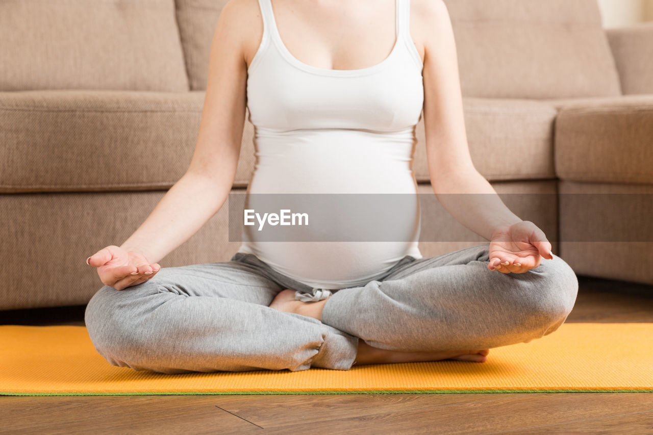 MIDSECTION OF WOMAN SITTING ON WOOD