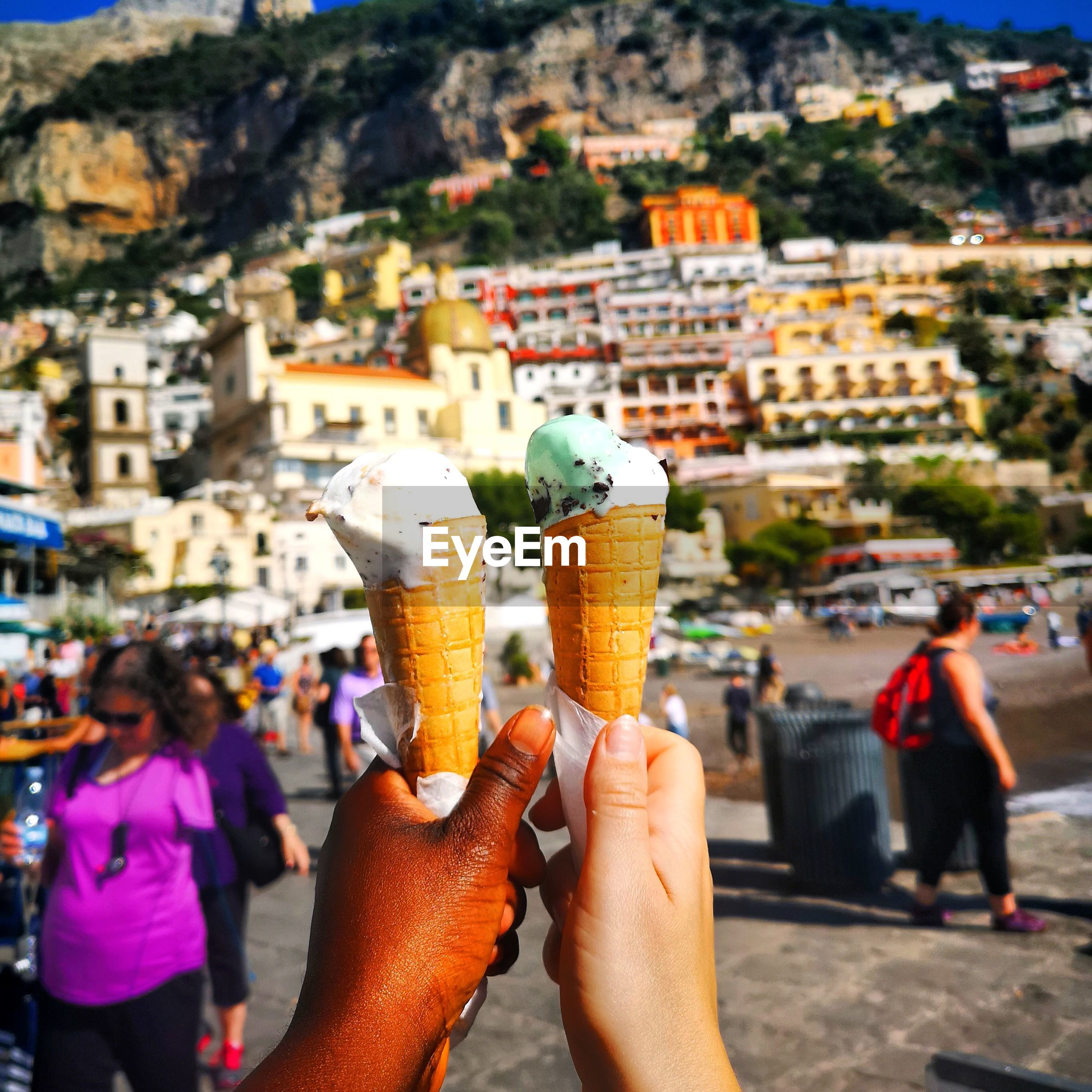 Close-up of man and woman holding ice cream in city