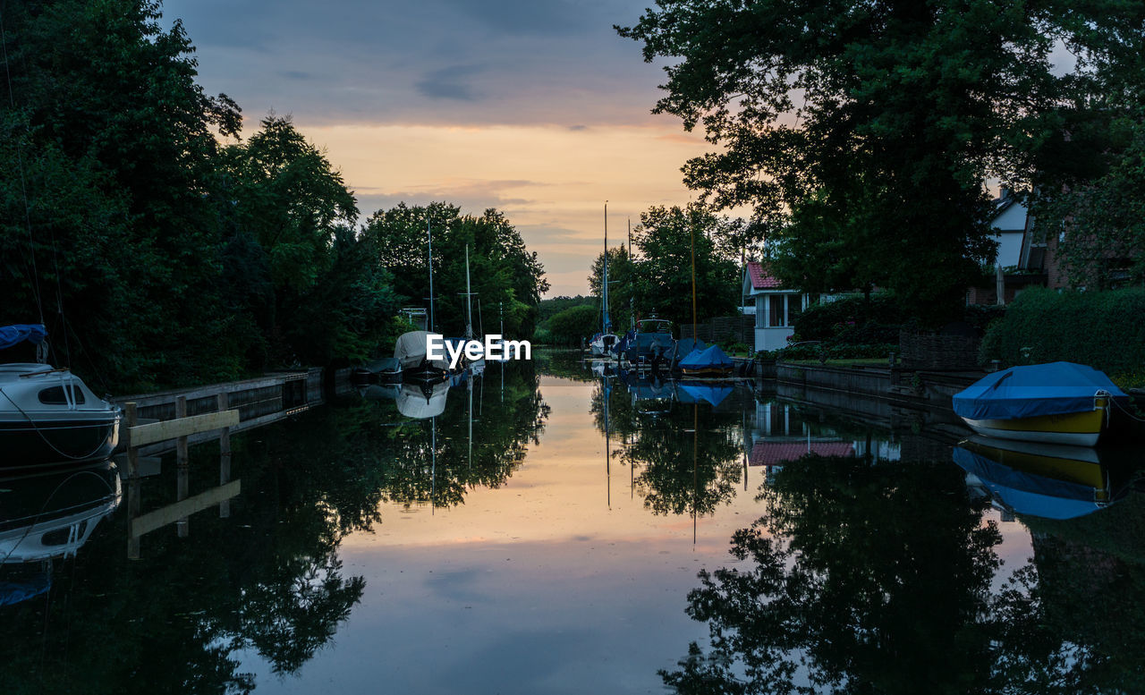 Boats Moored By Trees Against Sky During Sunset