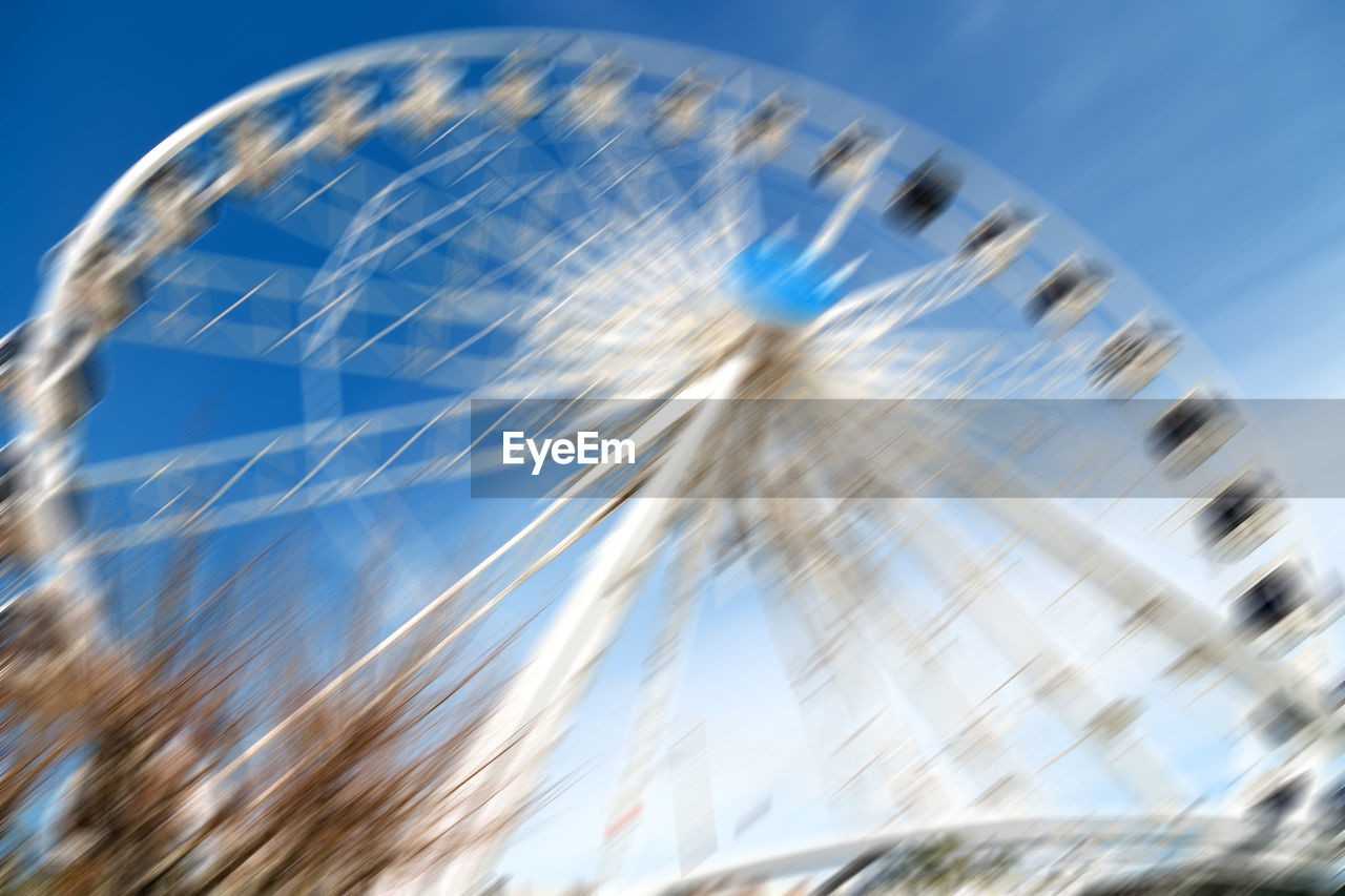 amusement park ride, blurred motion, amusement park, low angle view, ferris wheel, day, sky, nature, motion, no people, blue, arts culture and entertainment, clear sky, outdoors, leisure activity, speed, selective focus, spinning, sunlight, close-up, fairground