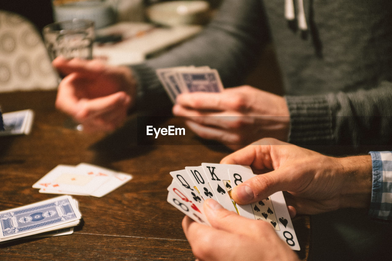 People Playing Cards At Table