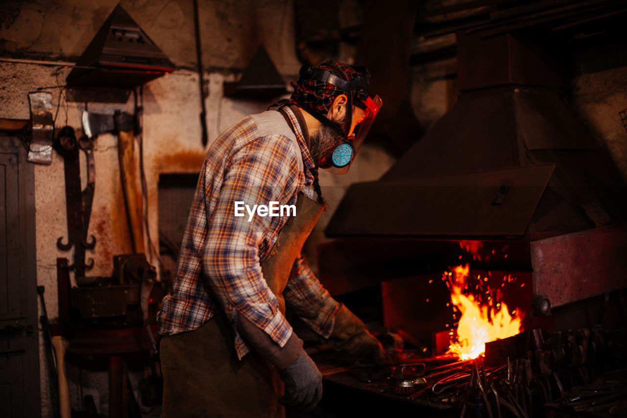 Side view of blacksmith working at workshop