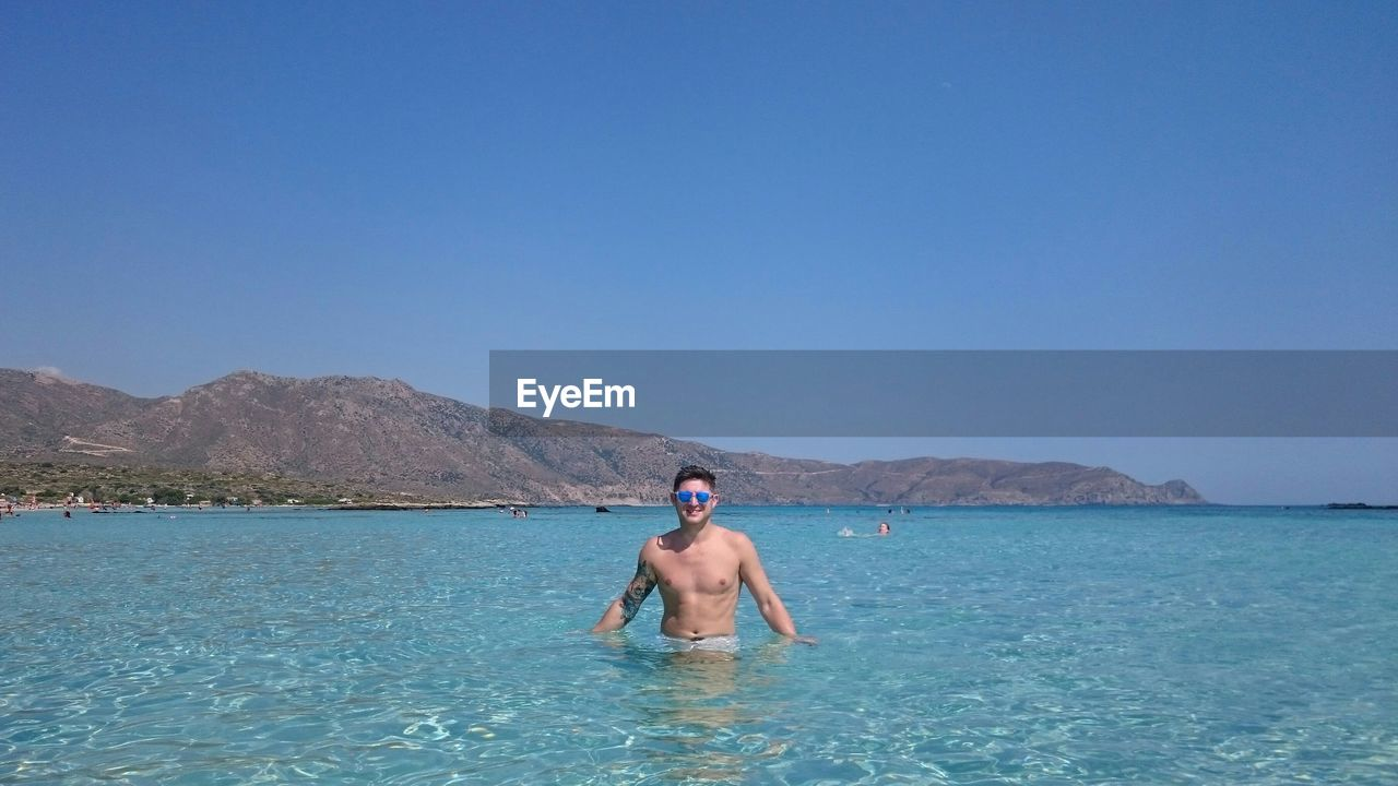 Shirtless Young Man Standing In Sea Against Clear Sky