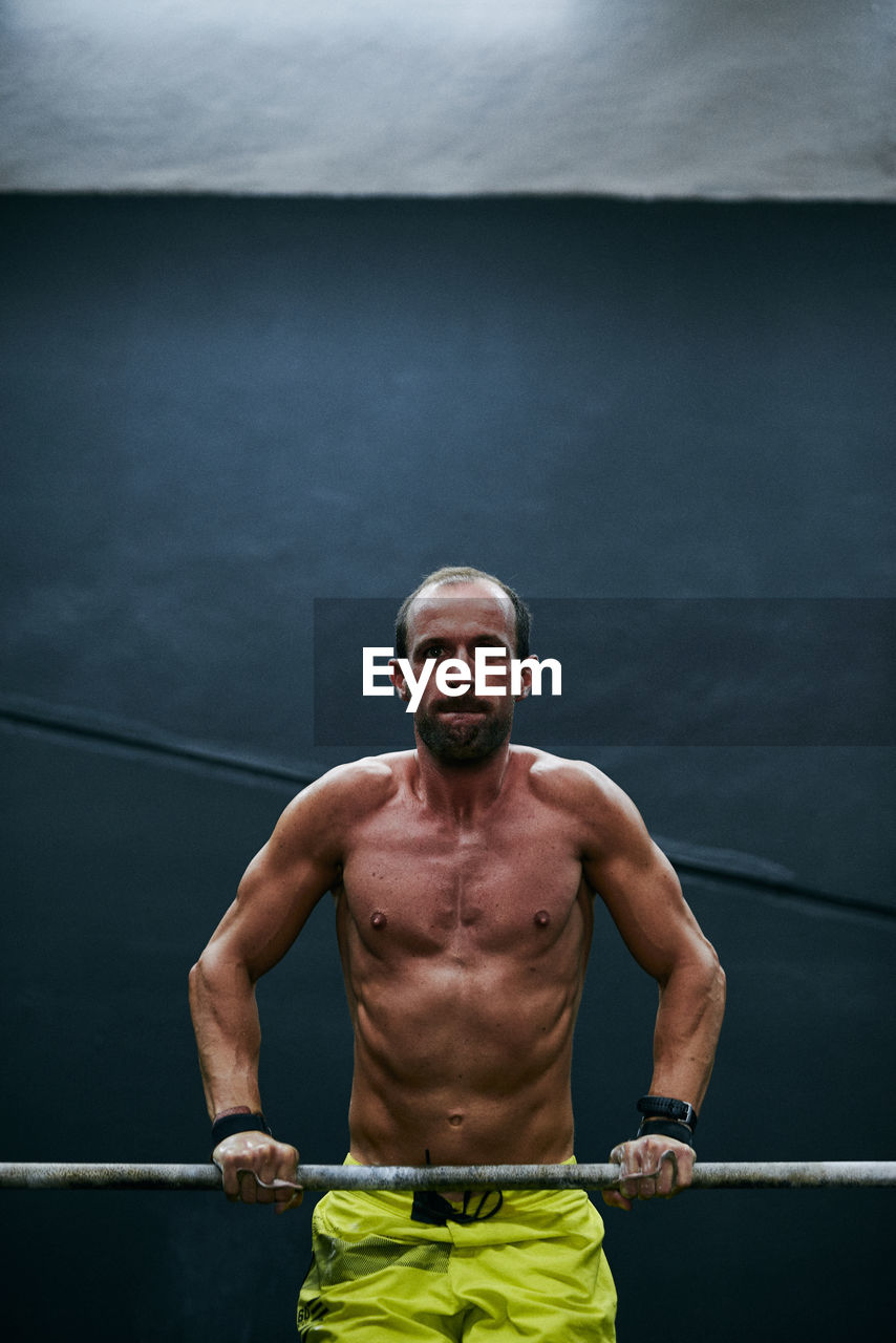 PORTRAIT OF SHIRTLESS MAN STANDING AGAINST THE WALL