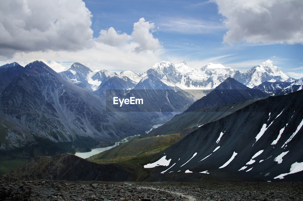 Top view from the pass to the mountain gorge and mount belukha in the snow in summer