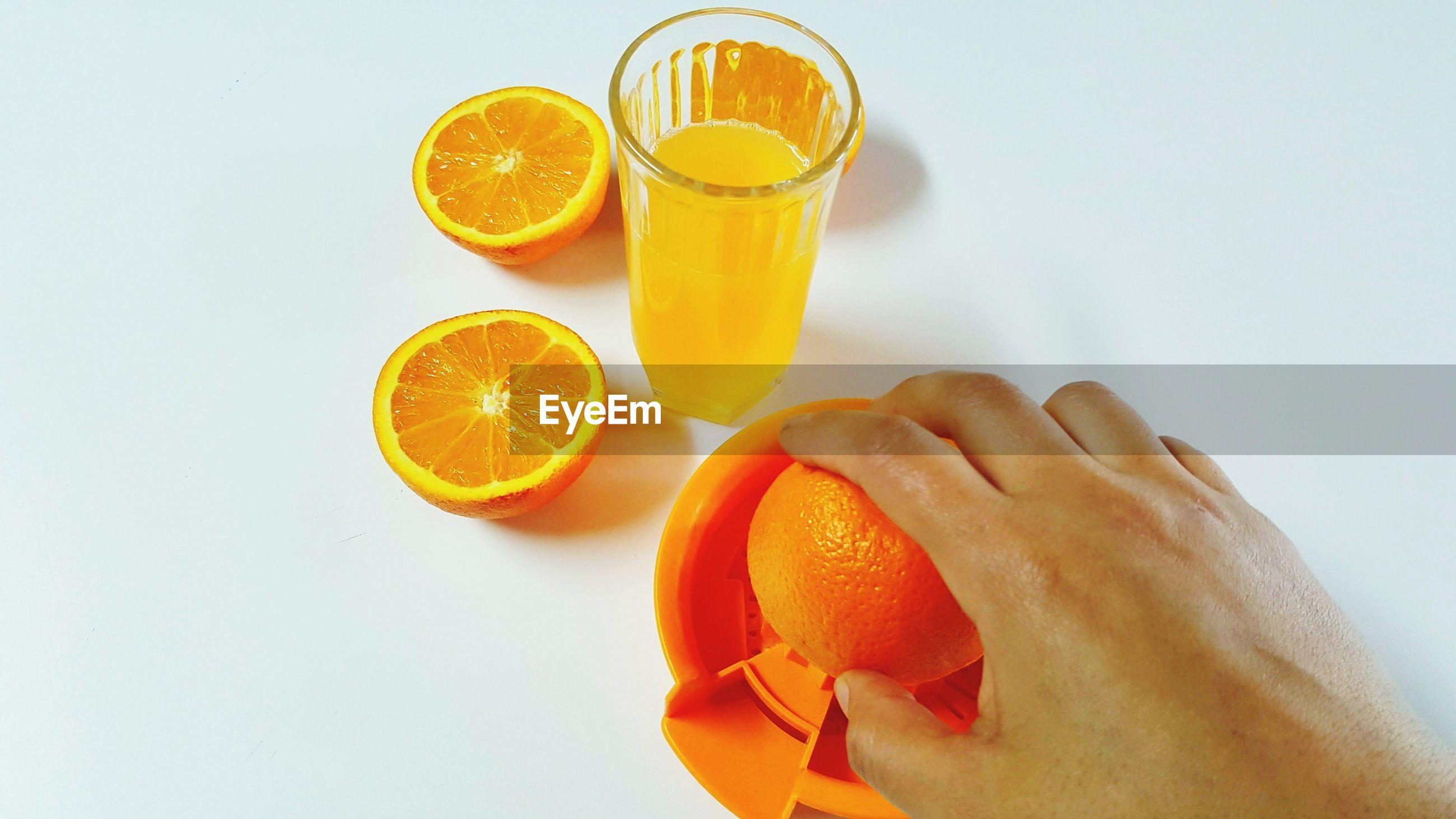 Close-up of cropped hand preparing orange juice against white background