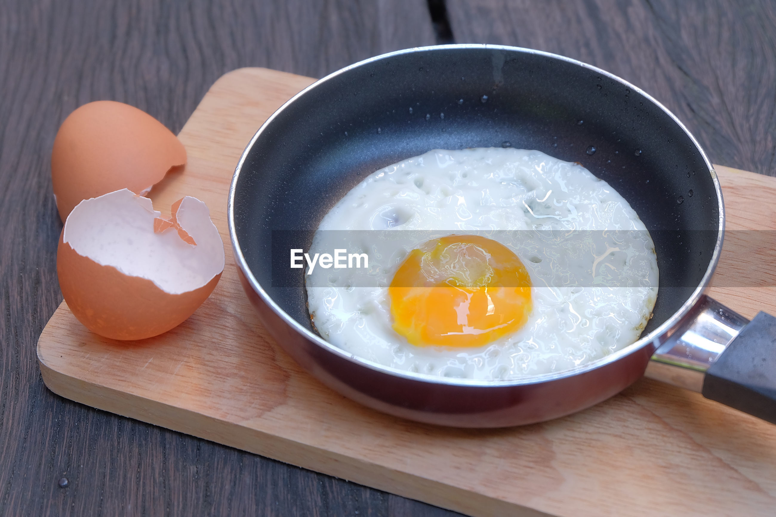 High angle view of egg in cooking pan on cutting board