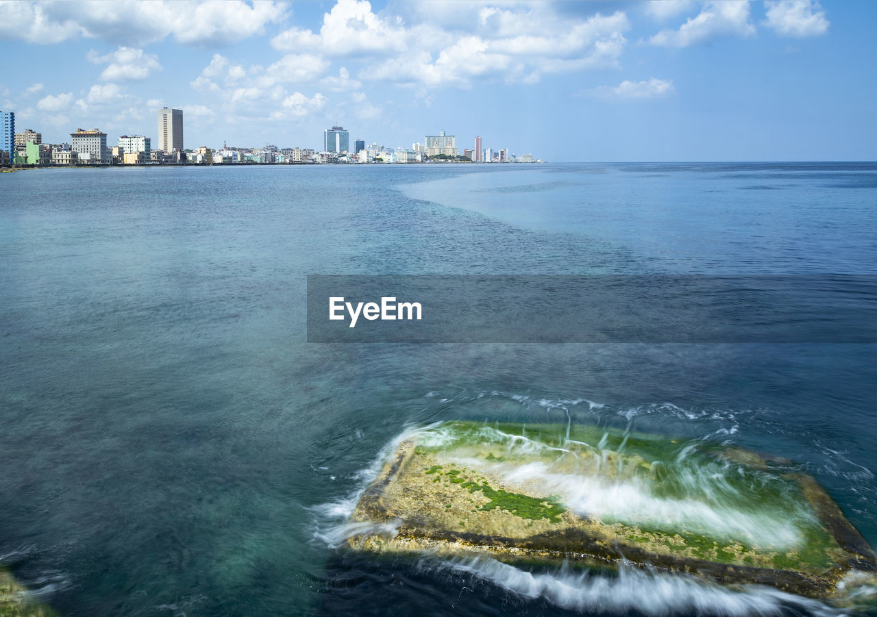 water, sky, sea, built structure, architecture, building exterior, cloud - sky, nature, waterfront, no people, scenics - nature, beauty in nature, day, city, motion, outdoors, land, beach, building, skyscraper, office building exterior, horizon over water, cityscape