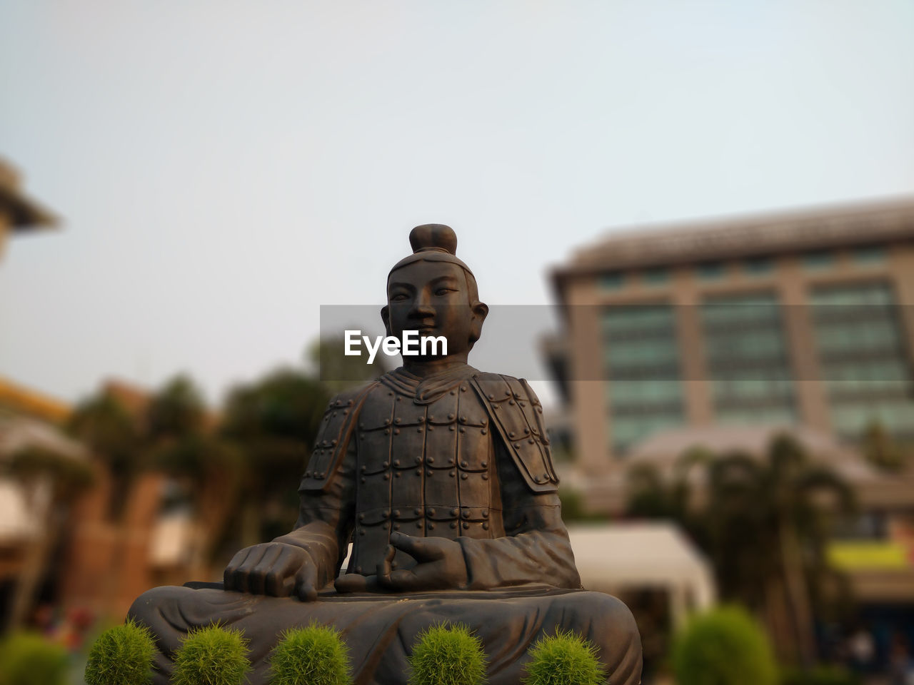 Low Angle View Of Buddha Statue Against Clear Sky In Park At Dusk