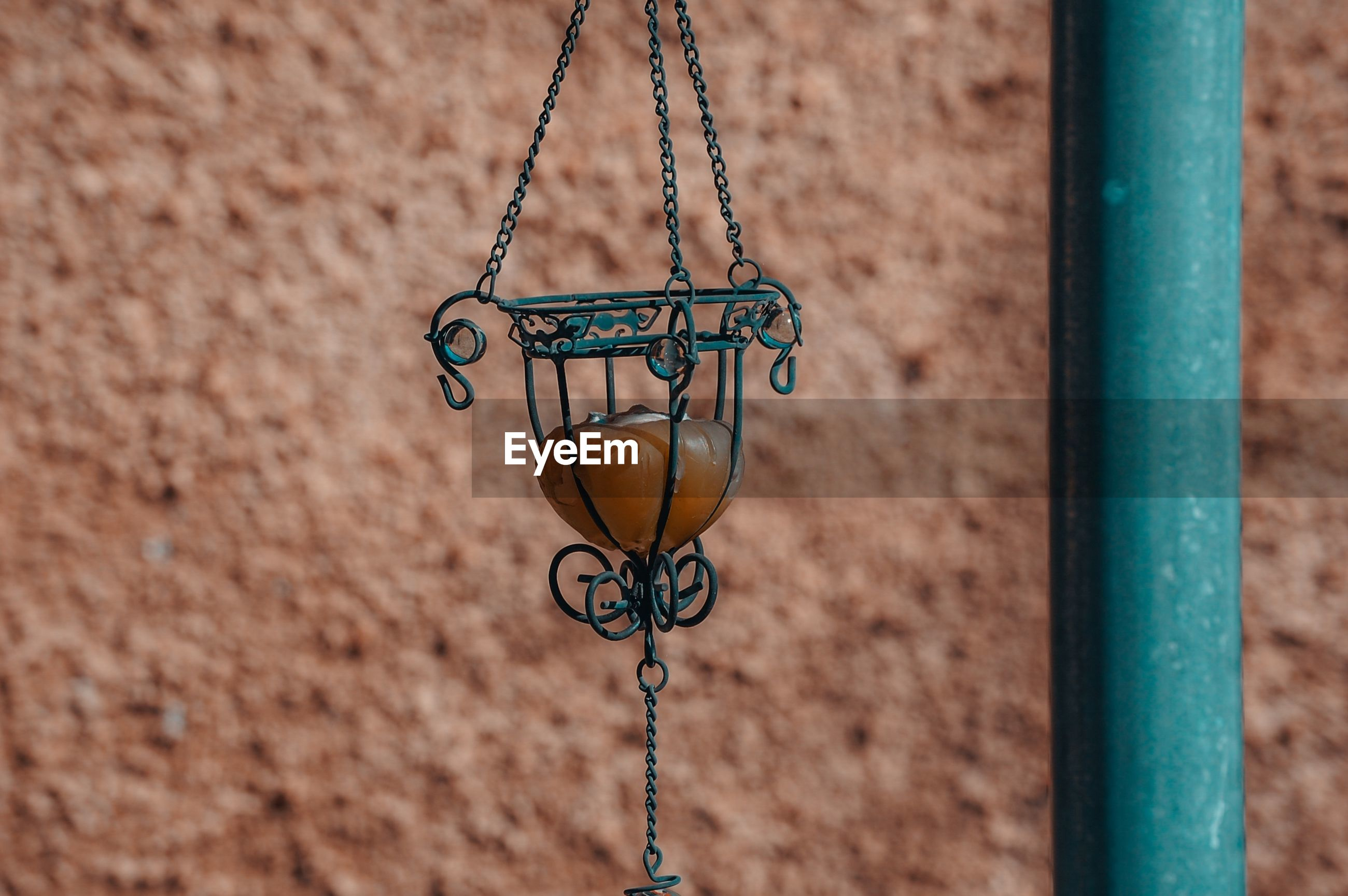 Close-up of lantern hanging against textured wall