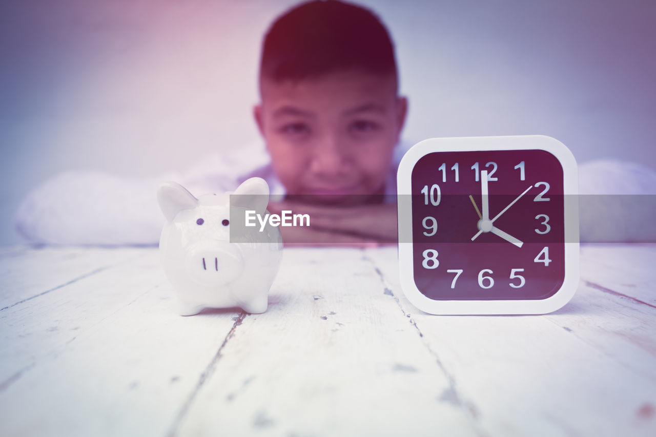 Portrait Of Teenage Boy By Piggy Bank And Clock On Table