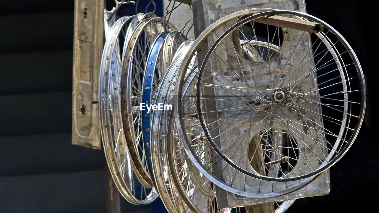 close-up, indoors, metal, no people, focus on foreground, still life, transportation, wheel, bicycle, mode of transportation, land vehicle, medium group of objects, shape, pattern, day, container, glass - material, stationary, spoke
