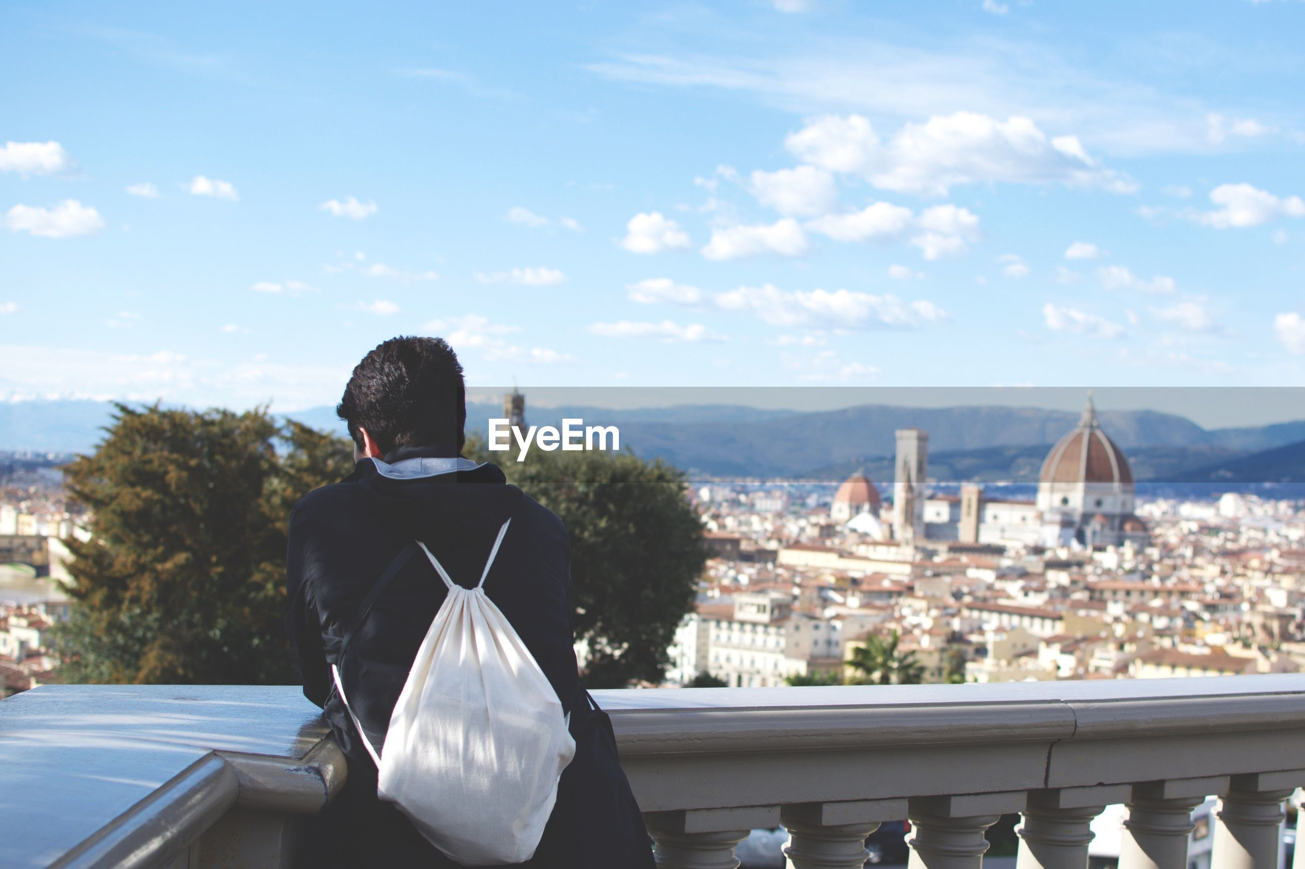 Rear view of man carrying backpack standing at observation point against cityscape