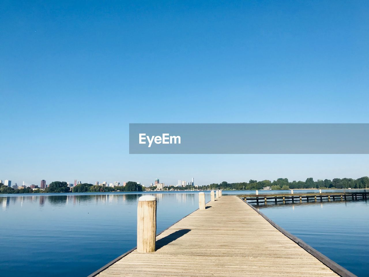 Pier Over Lake Against Clear Blue Sky