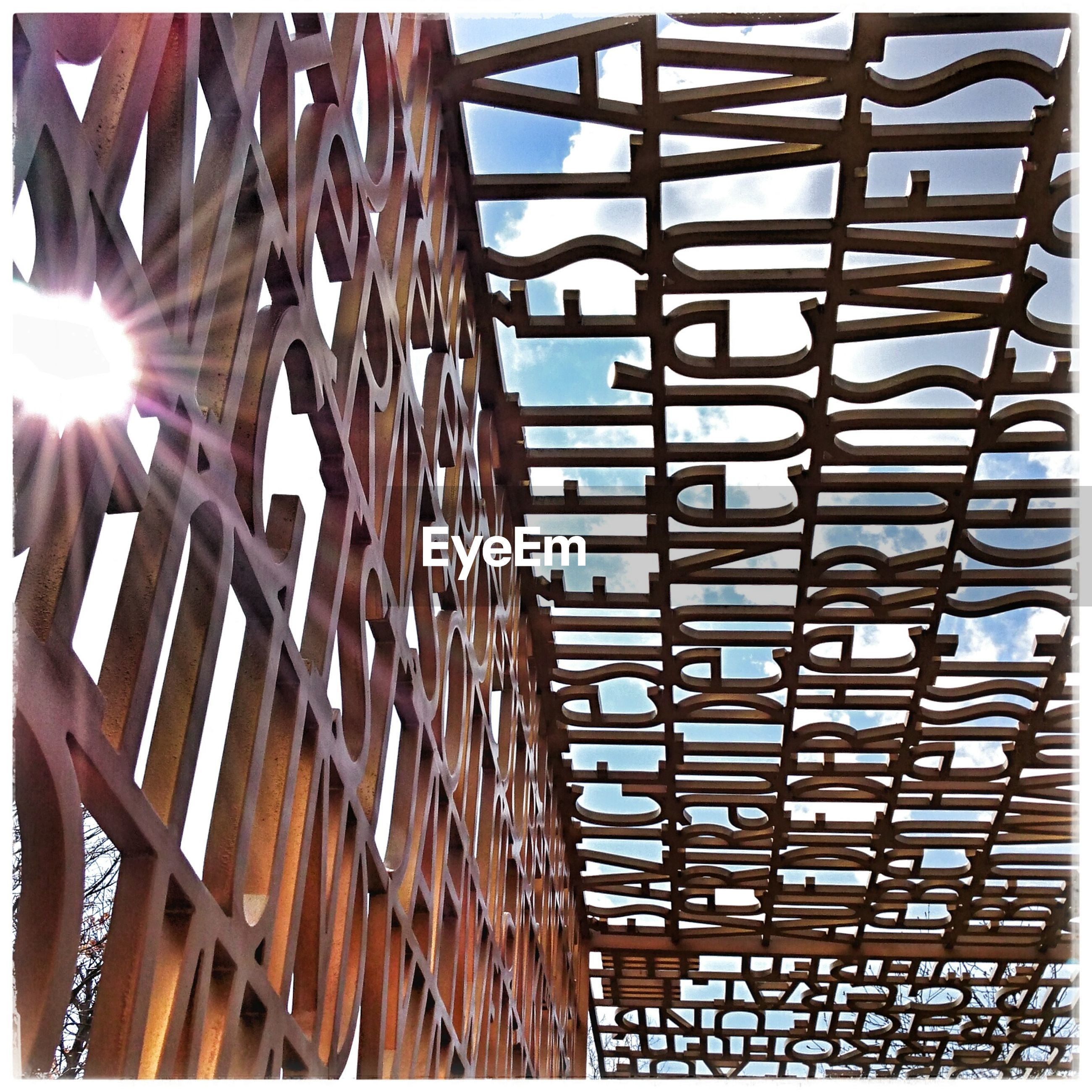 metal, built structure, low angle view, sunlight, architecture, railing, pattern, metallic, sunbeam, indoors, day, repetition, wood - material, in a row, shadow, no people, sunny, lens flare, ceiling